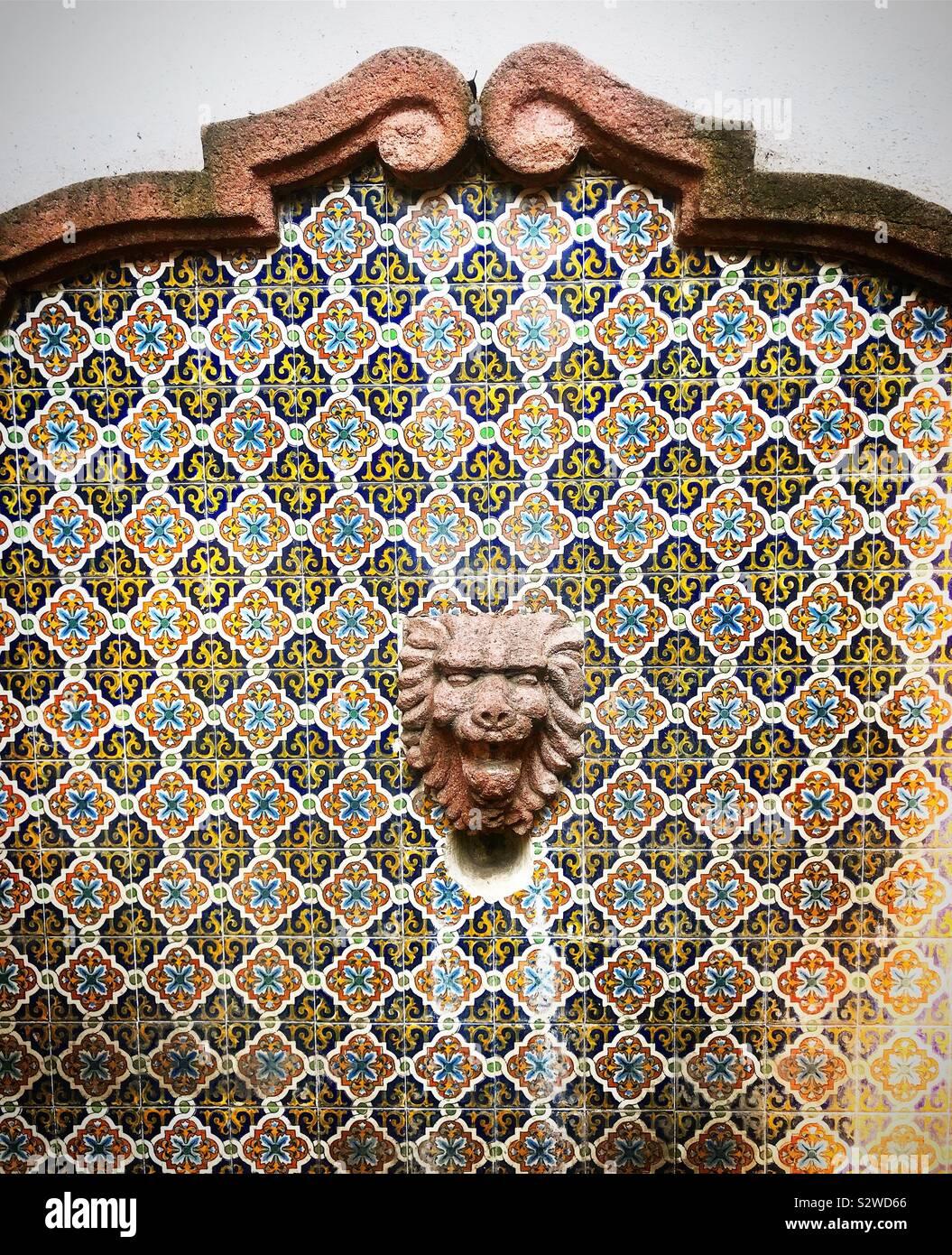 Una fontana decorata con figure geometriche di piastrelle di ceramica e di un leone in Coyoacan, Messico Foto Stock