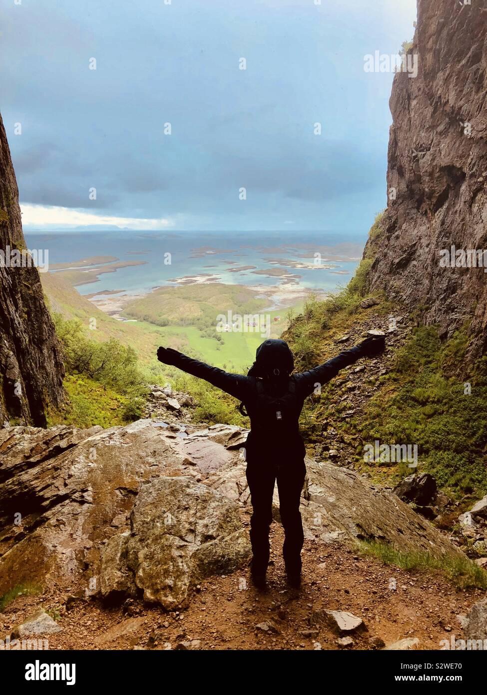 Donna che abbraccia il paesaggio, Torghatten grotta, Norvegia Foto Stock
