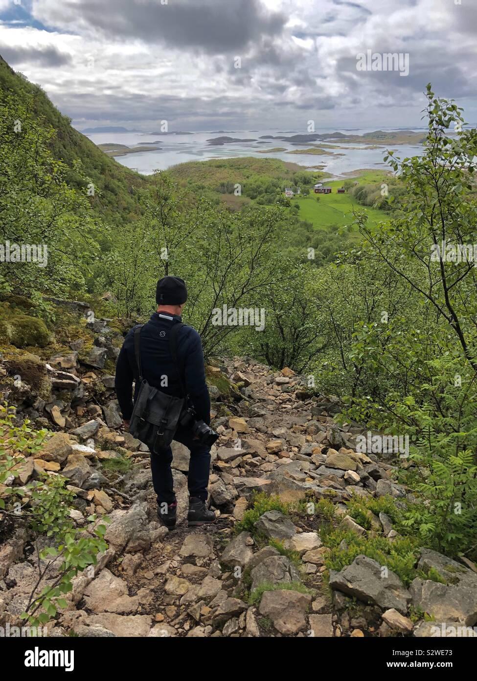 Uomo che cammina giù la via dalla grotta Torghatten, Norvegia Foto Stock
