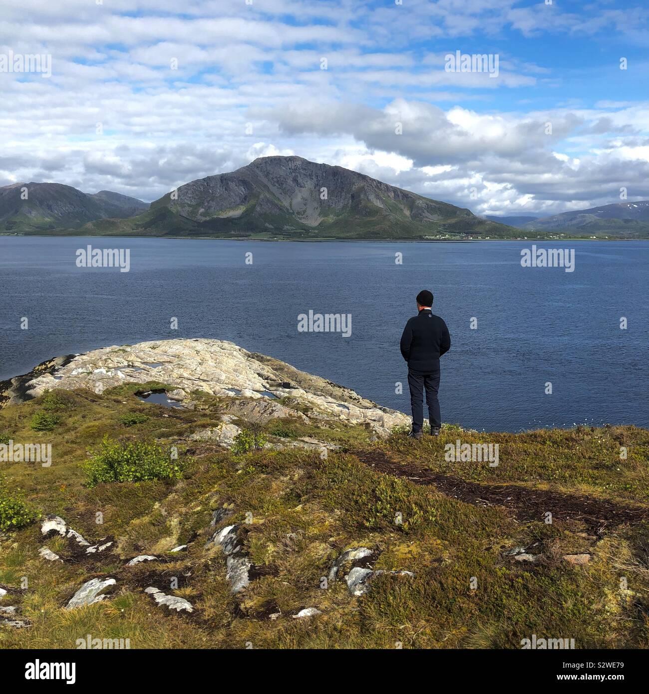 Uomo che guarda fuori attraverso un fiordo, Bronnoysund, Norvegia Foto Stock