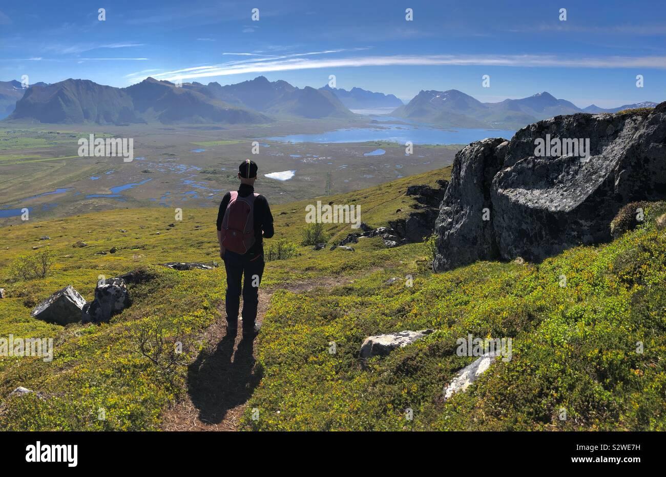 Uomo che cammina sul Monte Hoven, Gimsoya, Isole Lofoten in Norvegia Foto Stock