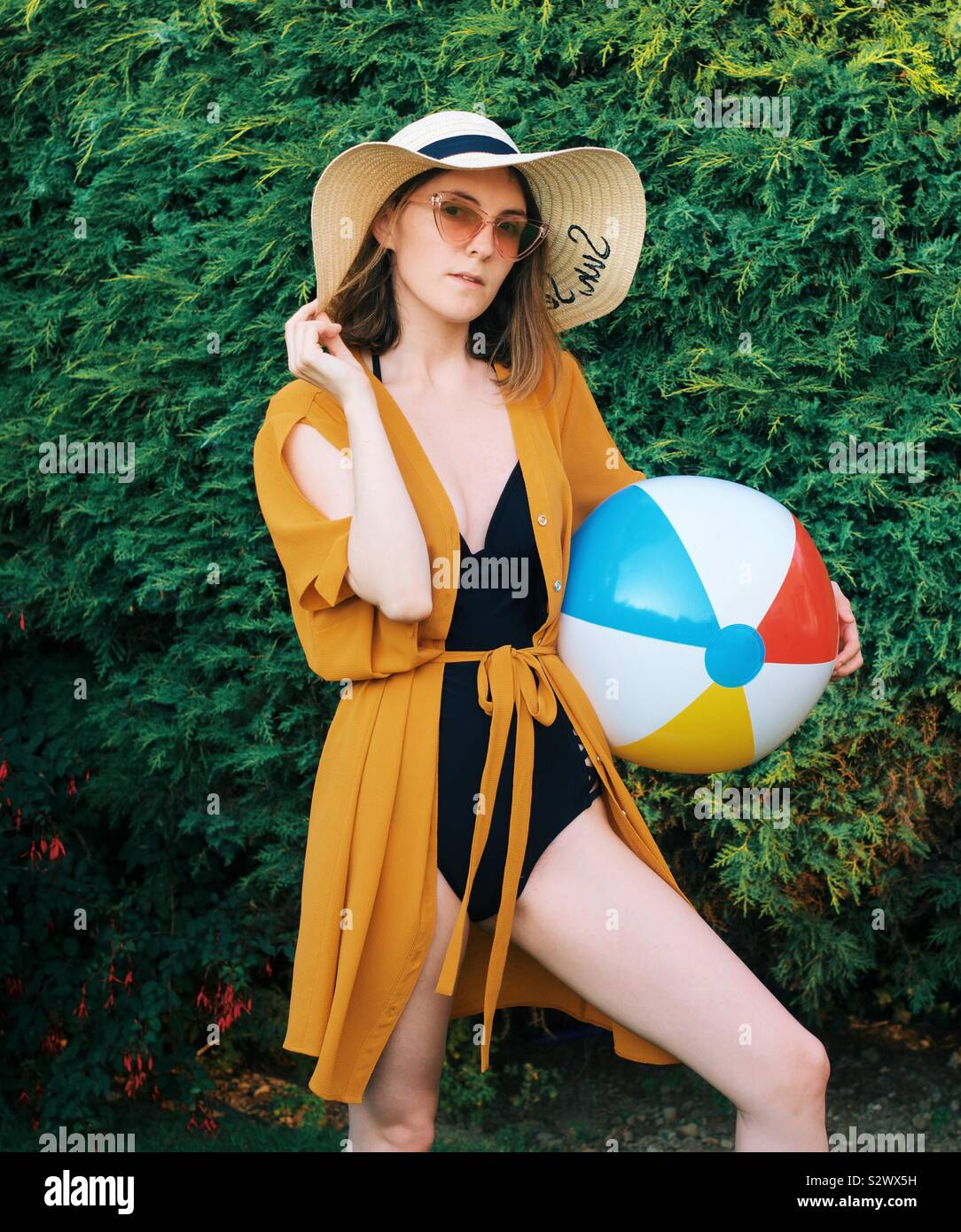 Ragazza con palla spiaggia in estate Foto Stock