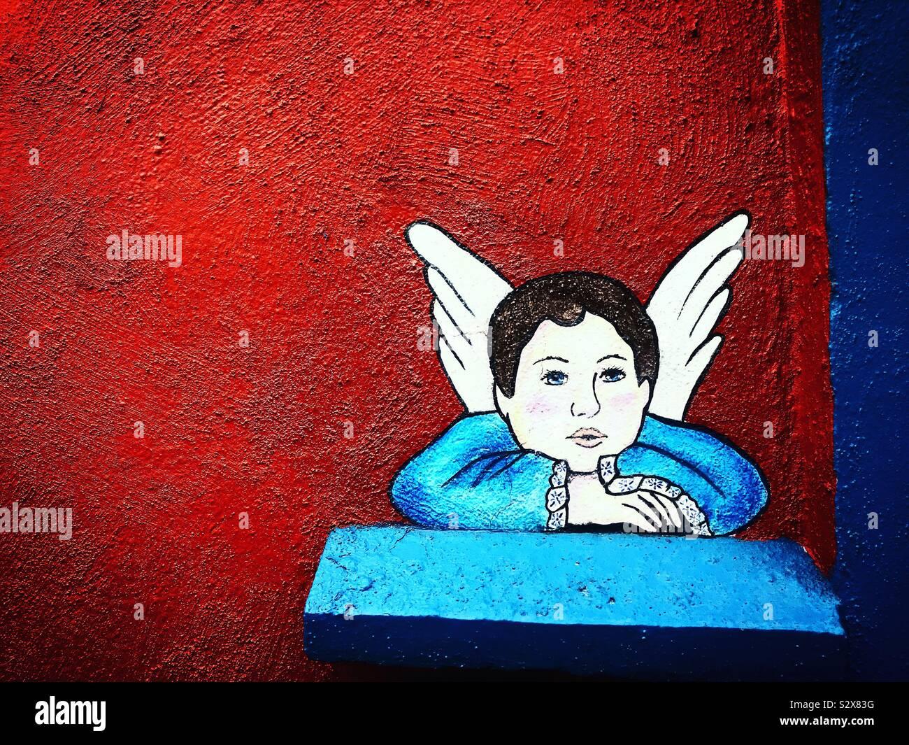 Una pittura di un cherubino blu in una parete rossa in una casa di San Angelo, Città del Messico, Messico Foto Stock