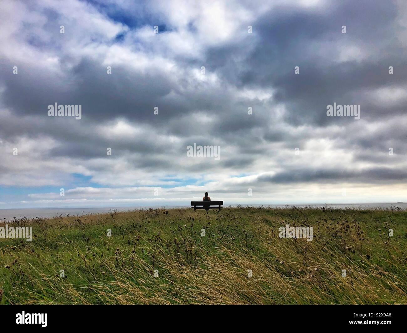 Giovane donna seduta su una panchina guardando il mare e il cielo. Foto Stock