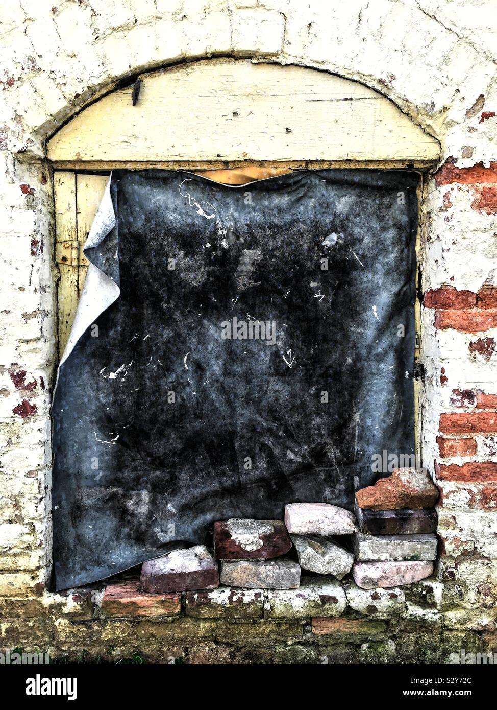 Un vecchio edificio abbandonato con un tessuto pesante copertura sopra il legno della porta anteriore. Foto Stock
