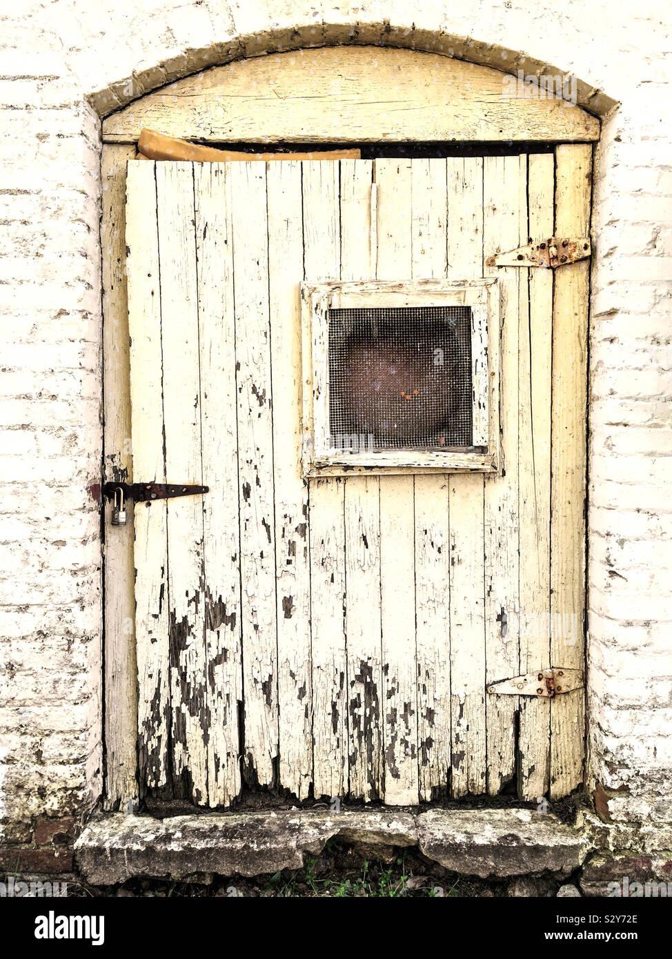 Un vecchio edificio abbandonato con una porta di legno che si sta deteriorando con l'età. Foto Stock