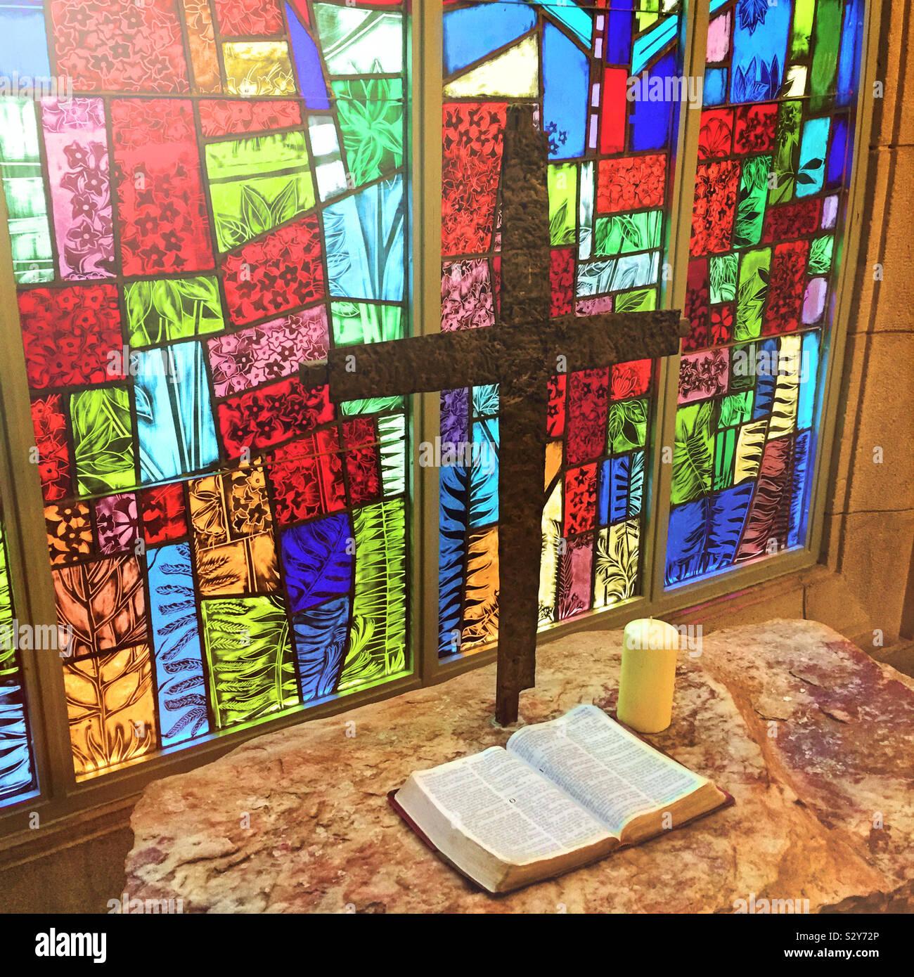 Coloratissima vetrata di illuminazione di una tabella in una chiesa che ha una croce religiosa e una Bibbia aperta su di esso. Foto Stock