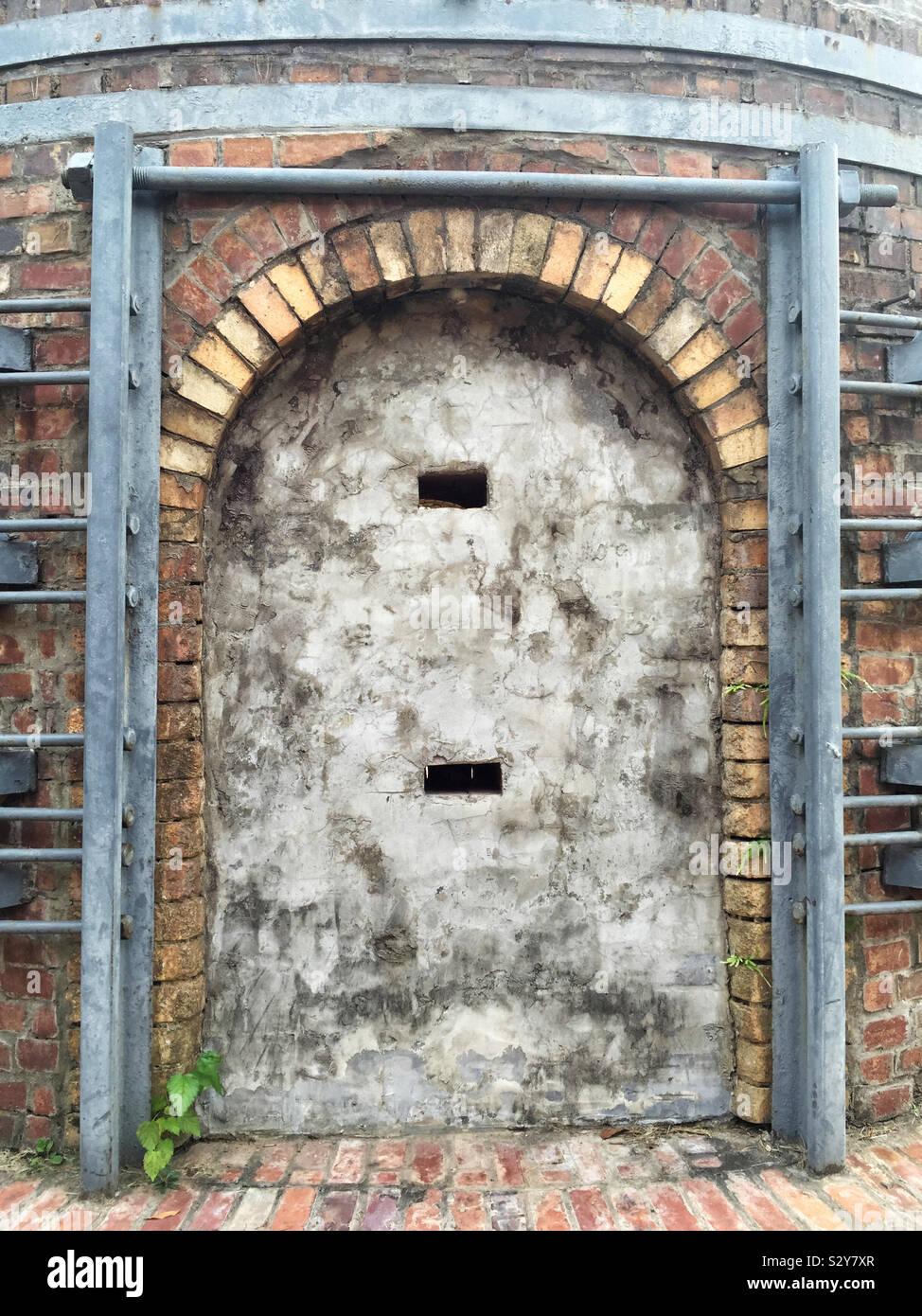 Un vecchio abbandonato edificio storico con una concreta porta. Esso ha due piccole aperture costruito in cemento. Foto Stock