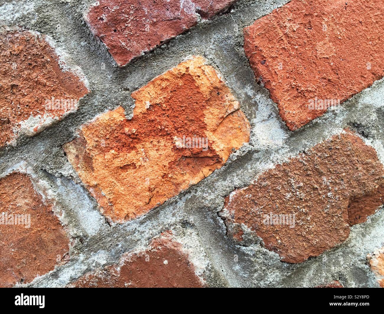 Un edificio storico costruito di grandi dimensioni e di colore rosso mattone con malta cementizia tenendolo insieme. Questa macro shot mostra tutti i dettagli e le texture. Foto Stock