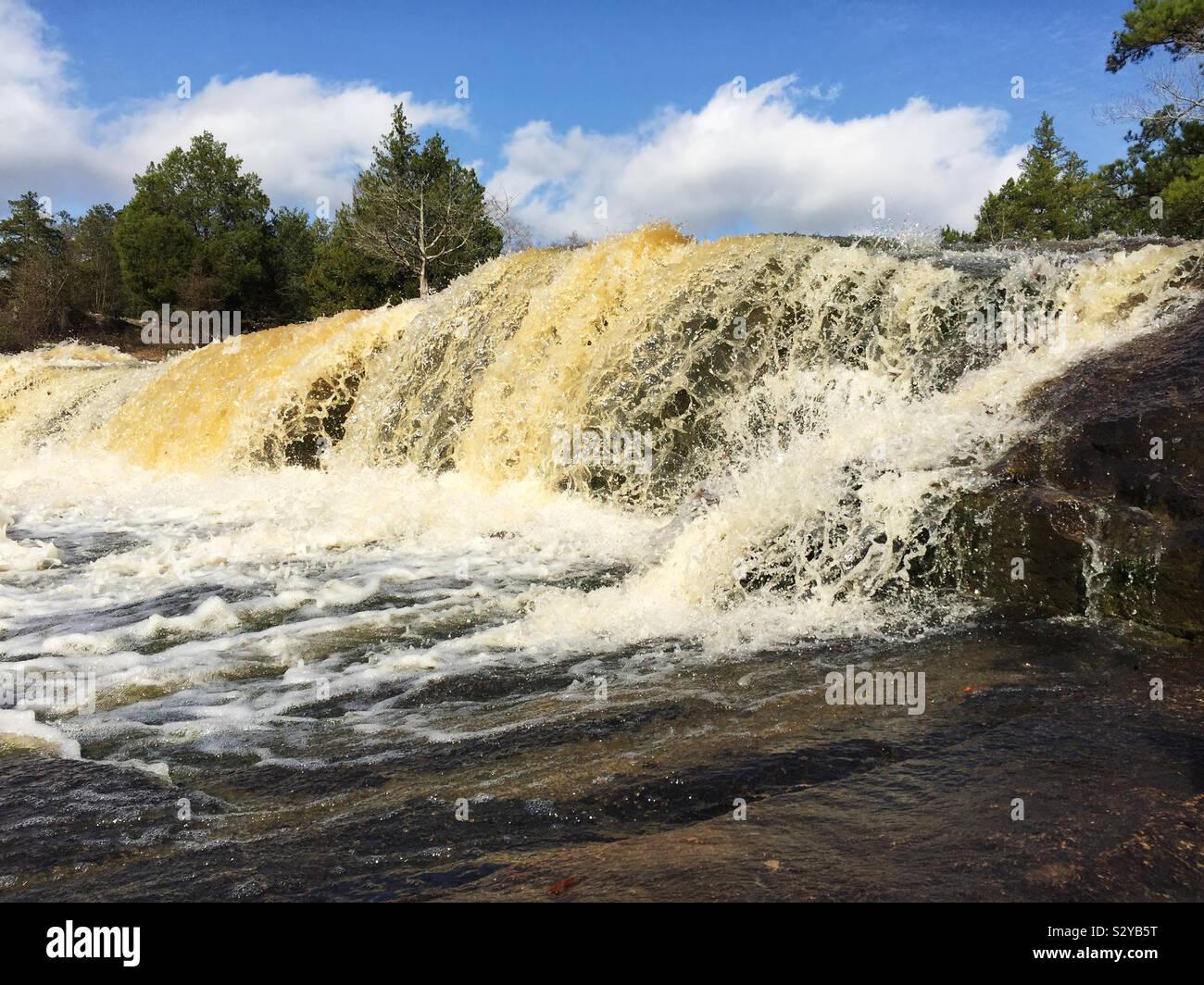 Che scorre veloce cascate e rocce intorno a una piscina esterna parco pubblico in Columbus Georgia USA dopo una forte pioggia. Foto Stock