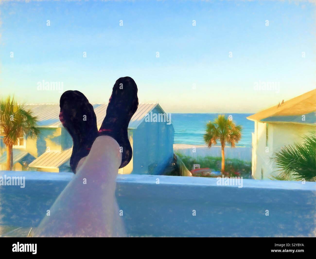 Una vista panoramica dell'oceano da una seconda fila condominiums balcone. Una donna ha i suoi piedi puntellato sul portico ringhiera. Questa immagine ha una texture pittorica di effetto. Foto Stock