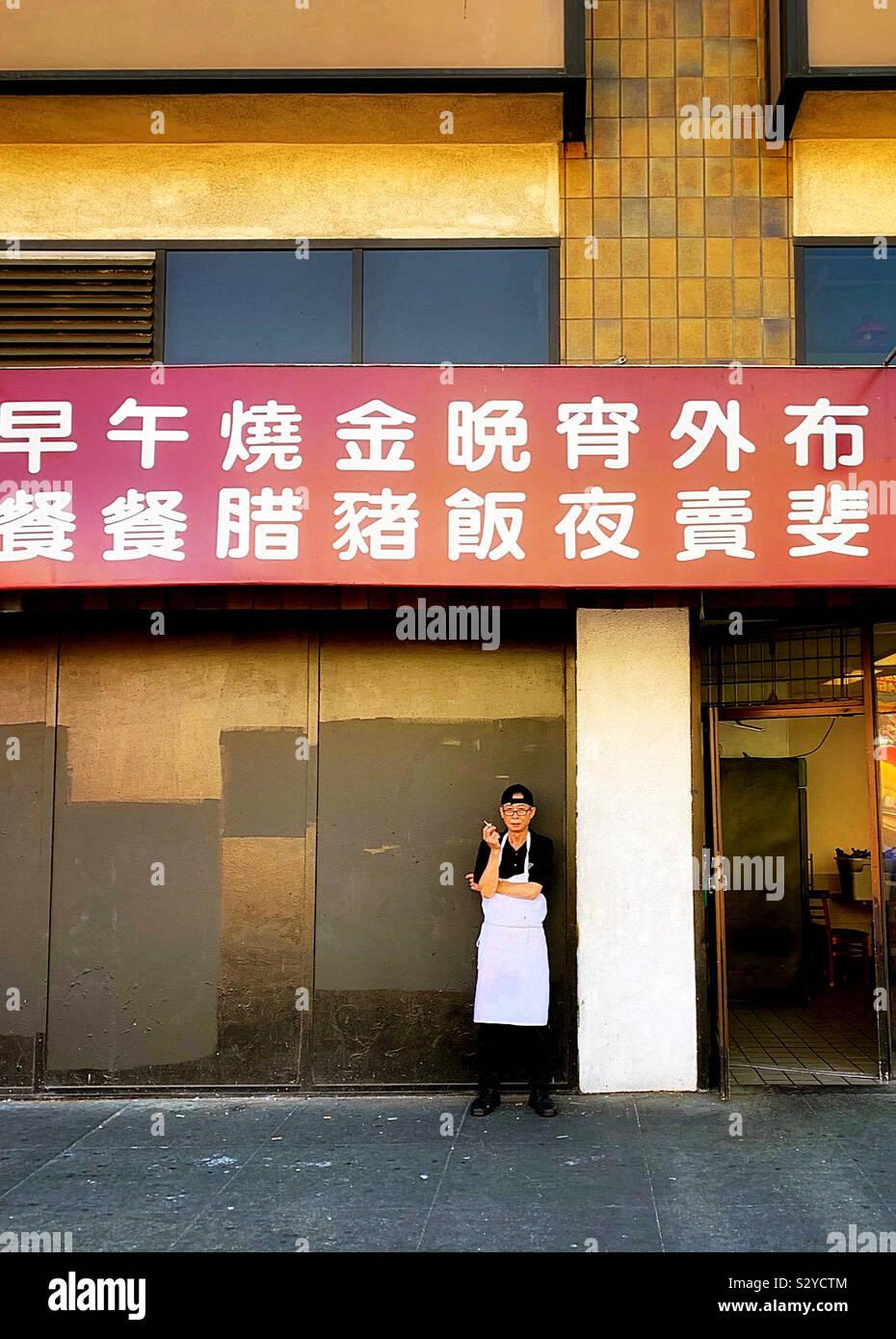 Il cuoco si fermò al di fuori il suo ristorante di lavoro per prendere la sua pausa per godersi il fumo Foto Stock