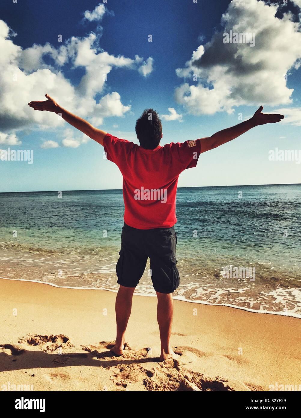 Un uomo in piedi su una bellissima spiaggia fino a raggiungere il cielo Foto Stock