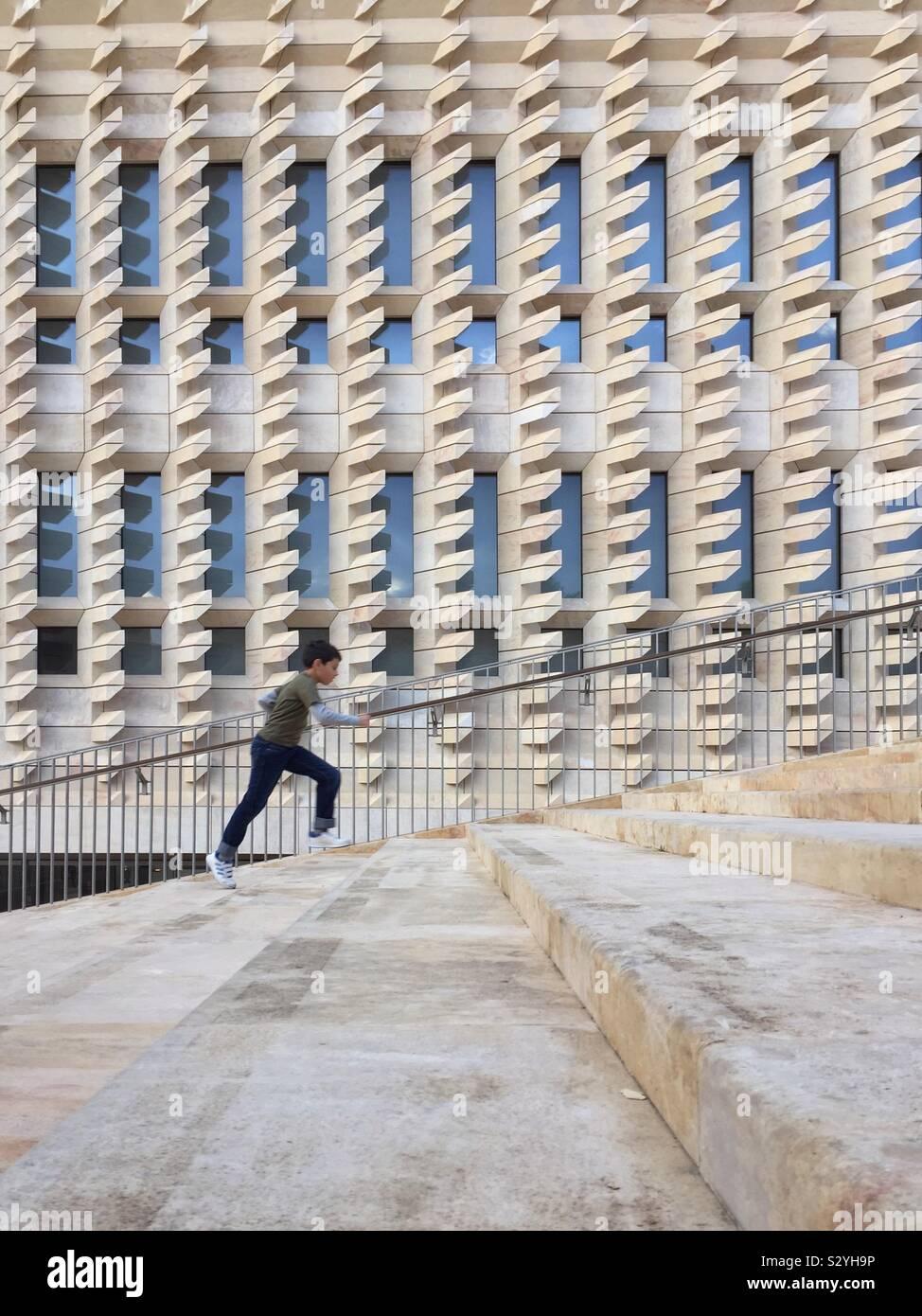 Ragazzo in esecuzione su per le scale fino a La Valletta, Malta. Renzo Piano dell'edificio in background Foto Stock