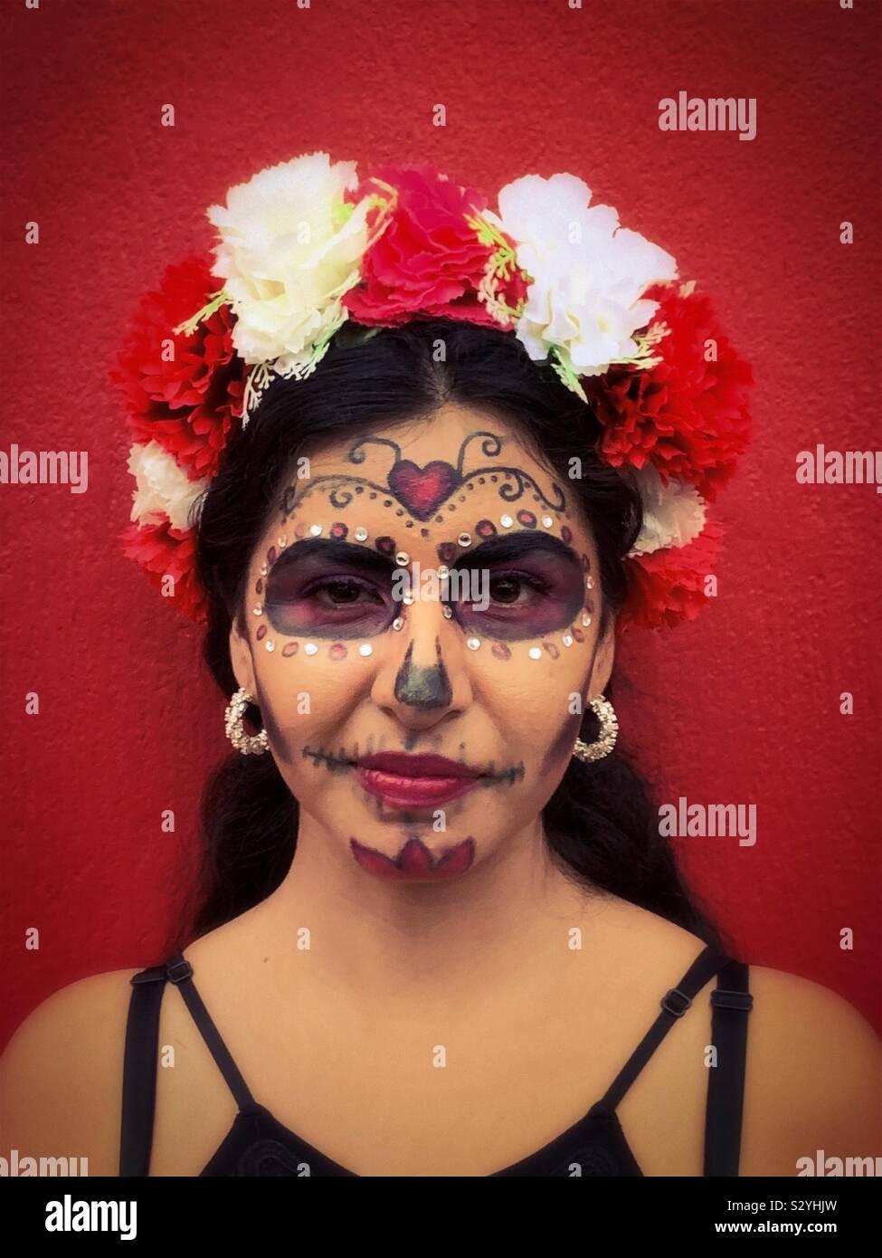 Una giovane donna con il suo volto dipinto come un catrina abiti fino ad una festa di Halloween in Ajijic, Messico. Foto Stock