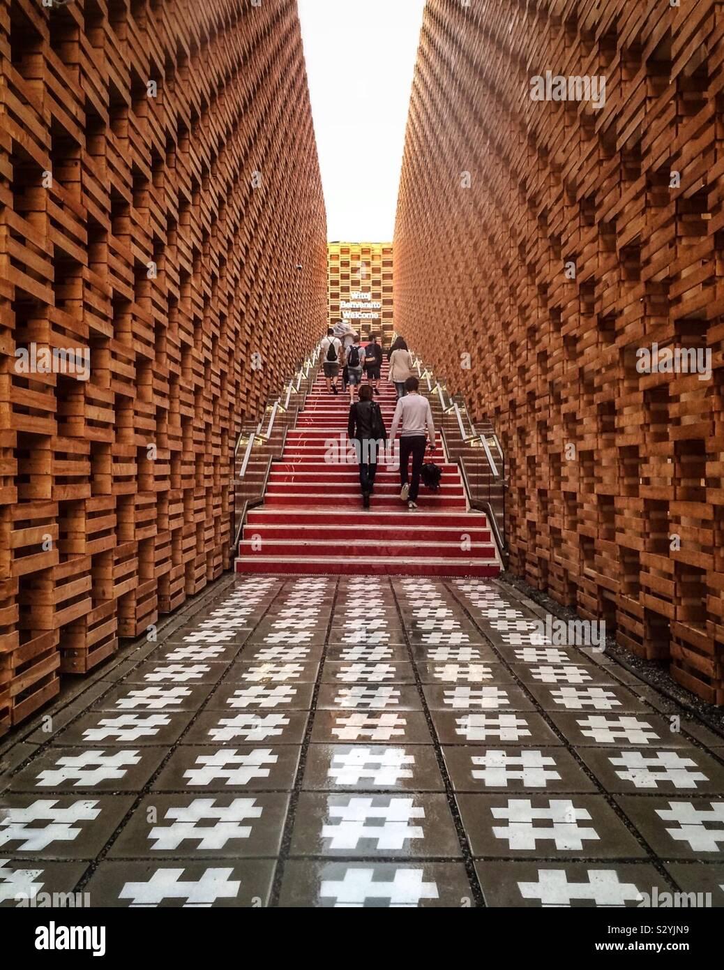 La gente a camminare su una scala tra le pareti in mattoni e un hashtag-pavimento a tema Foto Stock