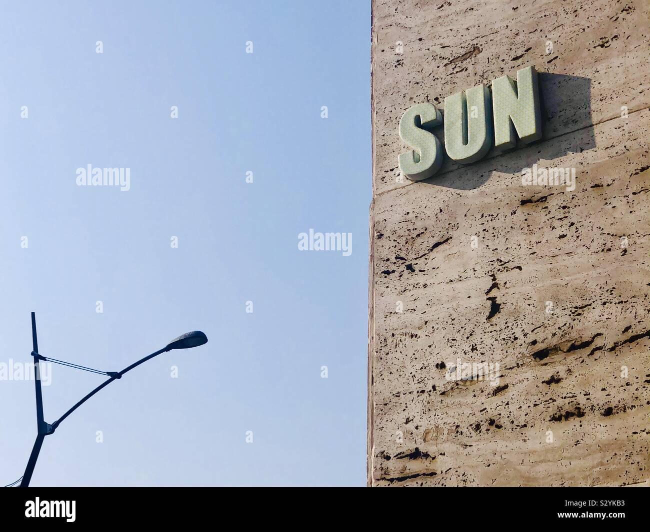 Il vecchio segno SUN di lettura sul lato di un edificio contro un cielo blu Foto Stock