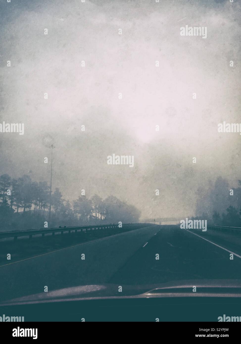 Un lugubre paesaggio riempito con nebbia mattutina su un triste giorno d'autunno durante la guida di un'auto. Questa immagine ha un grunge effetto testurizzato. Foto Stock