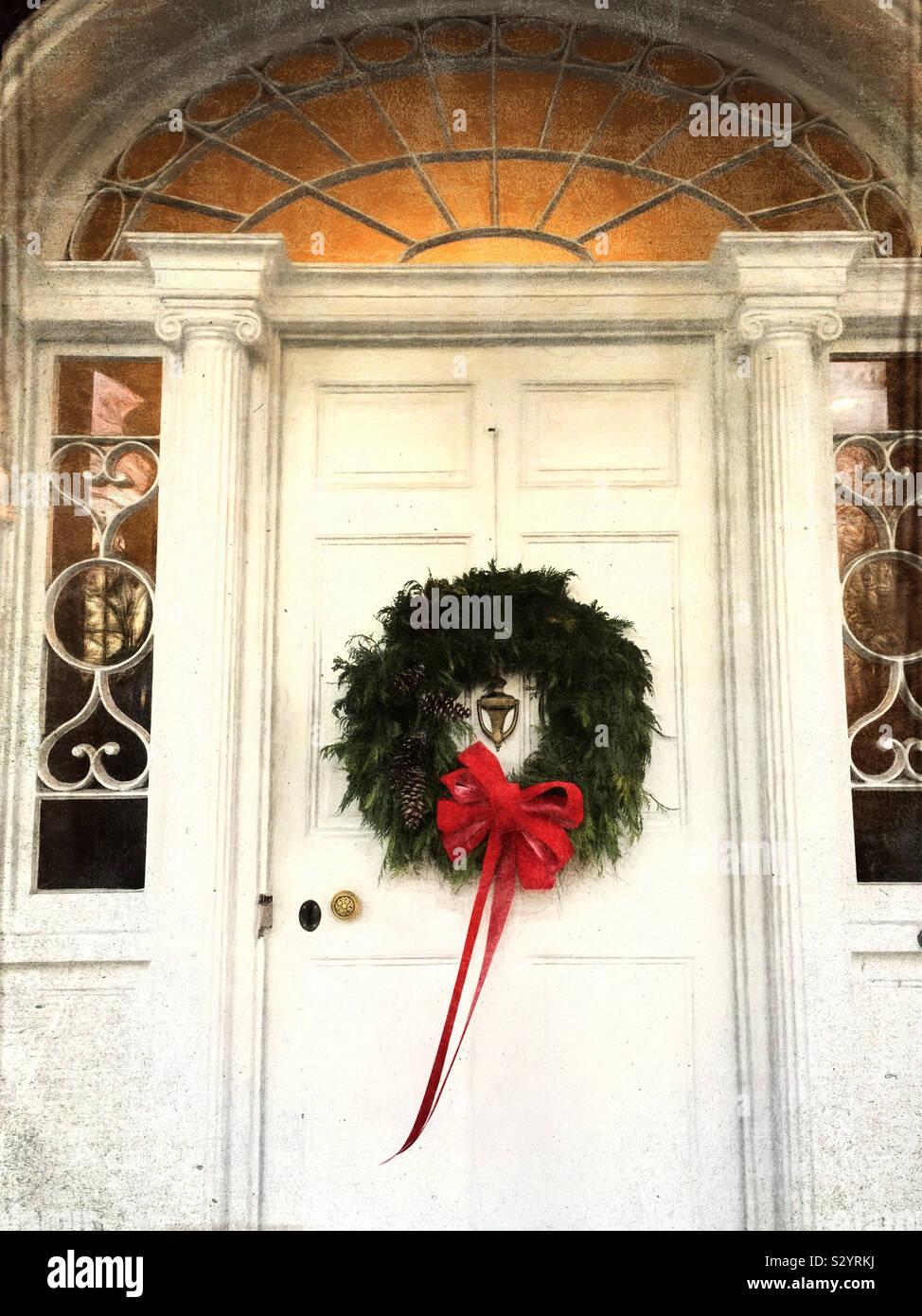 Un handmade vacanze di Natale corona è appeso su un colorato di bianco porta. Questa immagine ha una e pittorica di grunge effetto testurizzato. Foto Stock