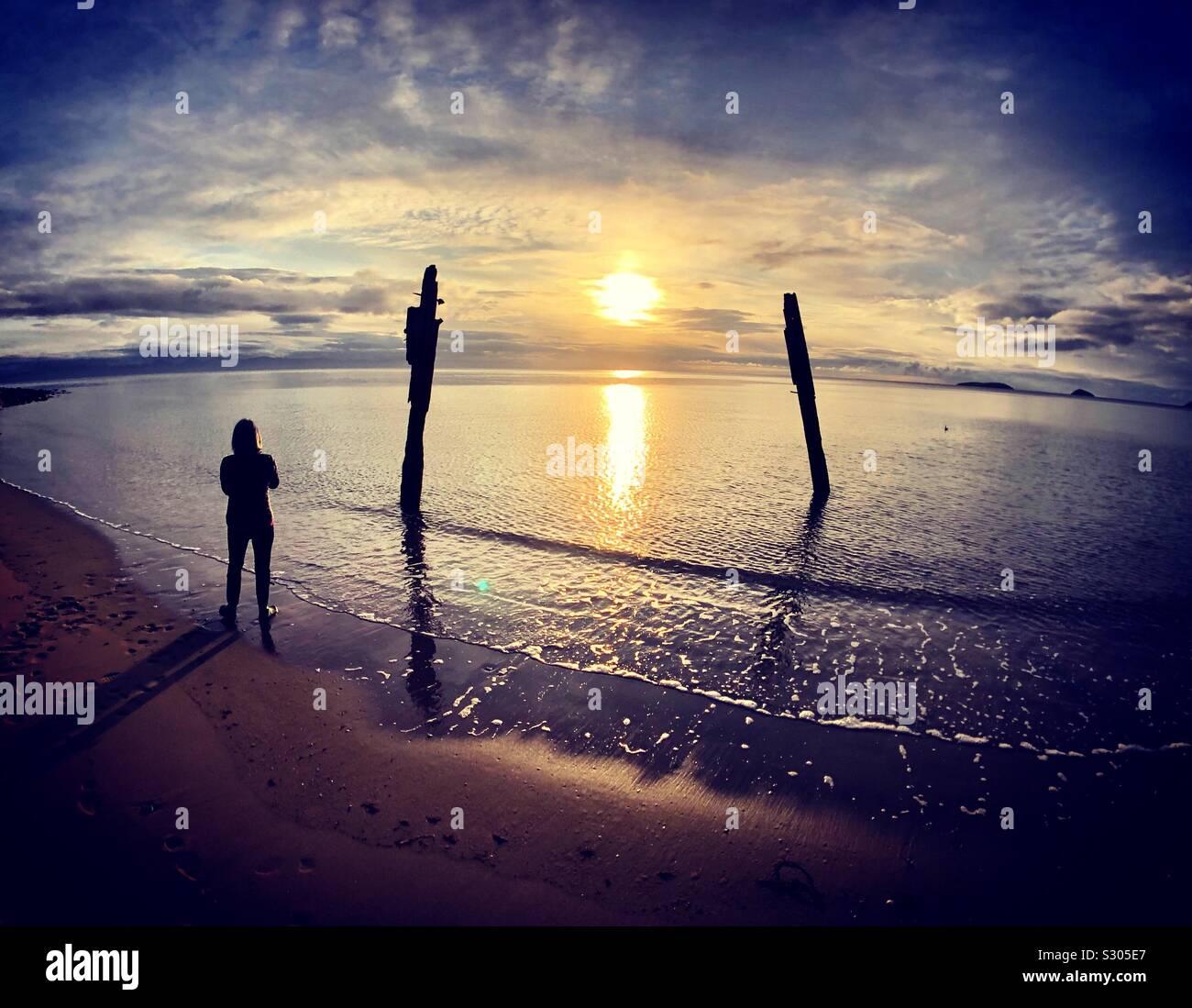 Donna di sunrise, Abersoch beach, Llanengan in Gwynedd, Galles Foto Stock