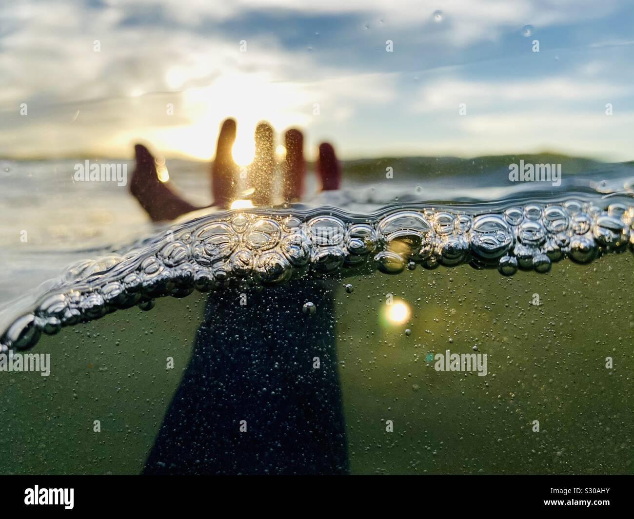 Un over-sotto la foto di una mano sinistra di uscire dall'acqua. Foto Stock
