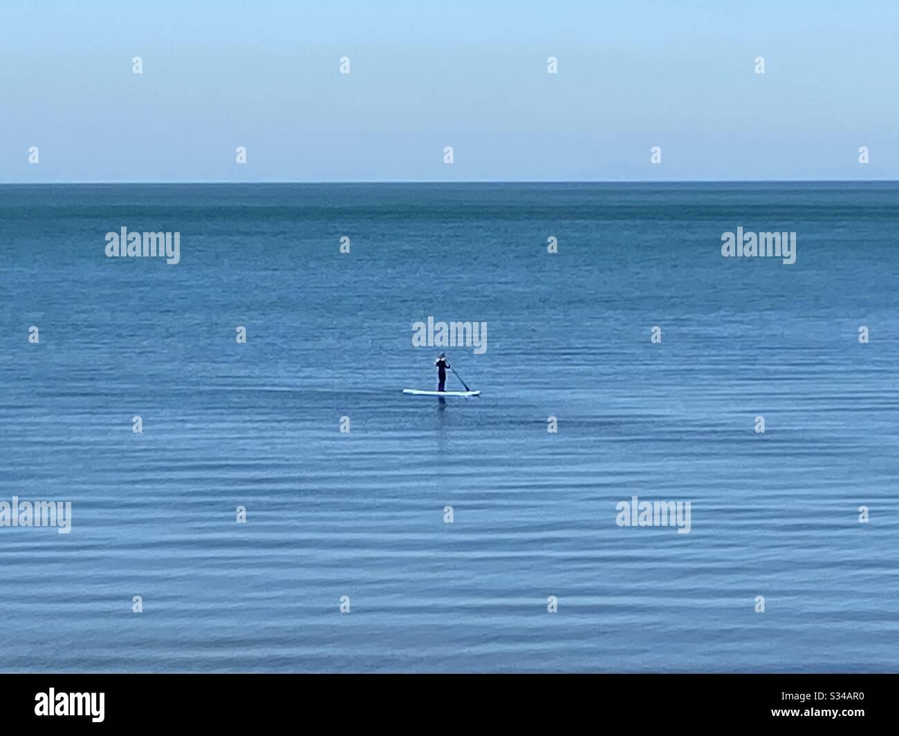Aberystwyth, Galles occidentale, Regno Unito. Domenica 22 marzo 2020. News: Un pomeriggio caldo e soleggiato, una persona è visto paddleboarding la domenica madre, il mare è calmo e tranquillo.©️Rose Voon/Alamy Live News Foto Stock