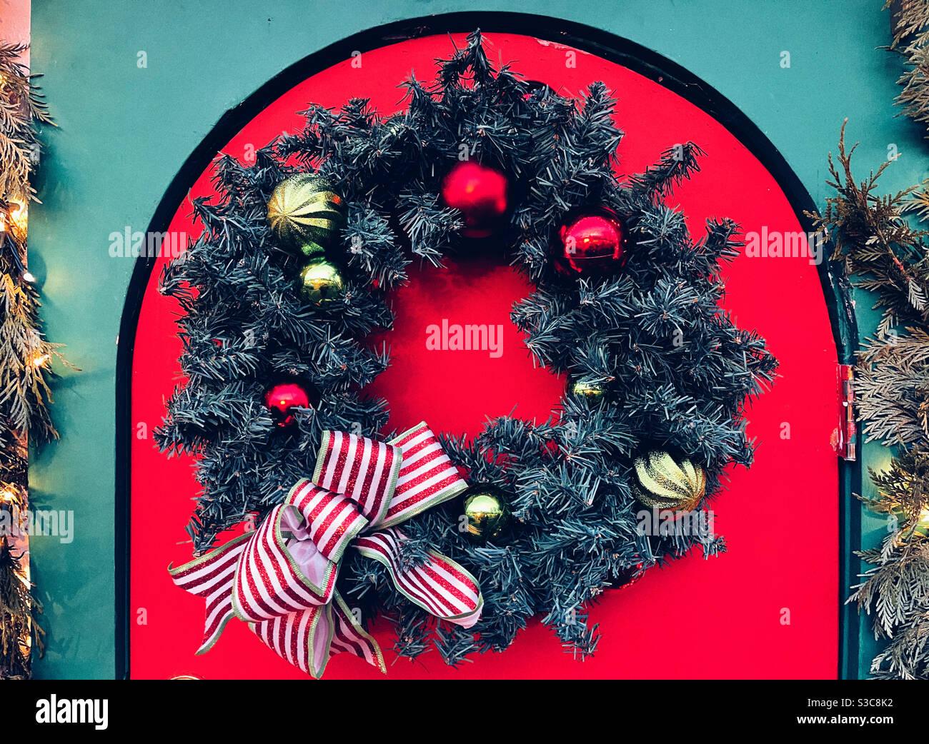 Ghirlanda di Natale sulla porta rossa Foto Stock
