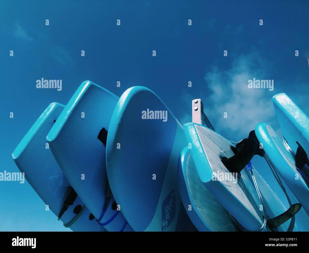 Tavole da surf blu contro il cielo blu in una scuola di surf Cornovaglia Foto Stock