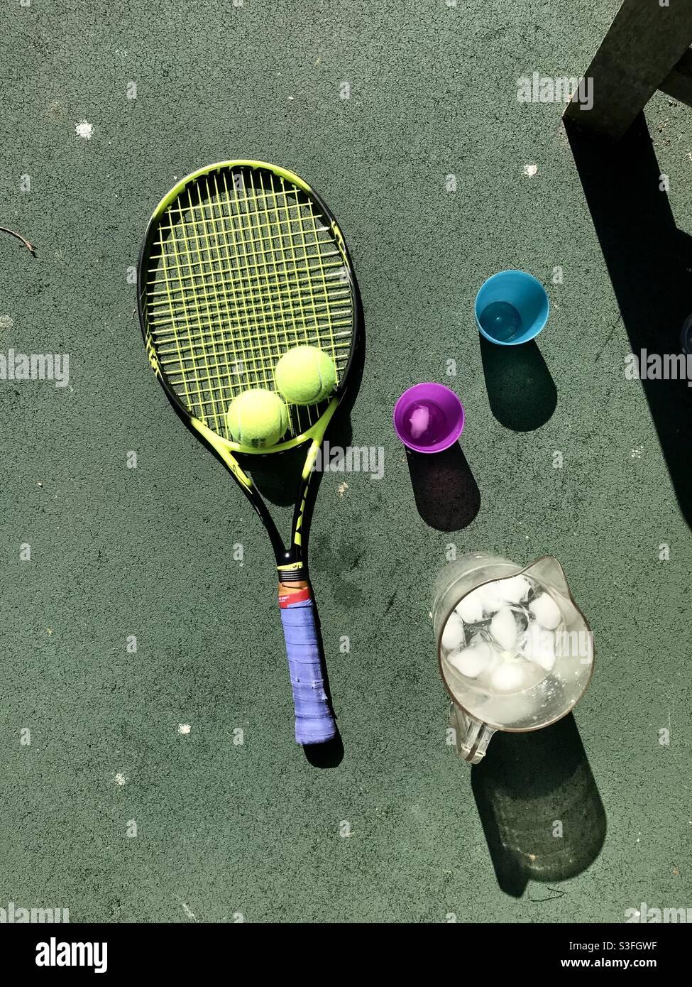 Vista a volo d'uccello delle racchette da tennis su un campo da tennis con palle da tennis a fianco una caraffa di ghiaccio freddo acqua e un paio di tazze su un caldo sole giorno Foto Stock