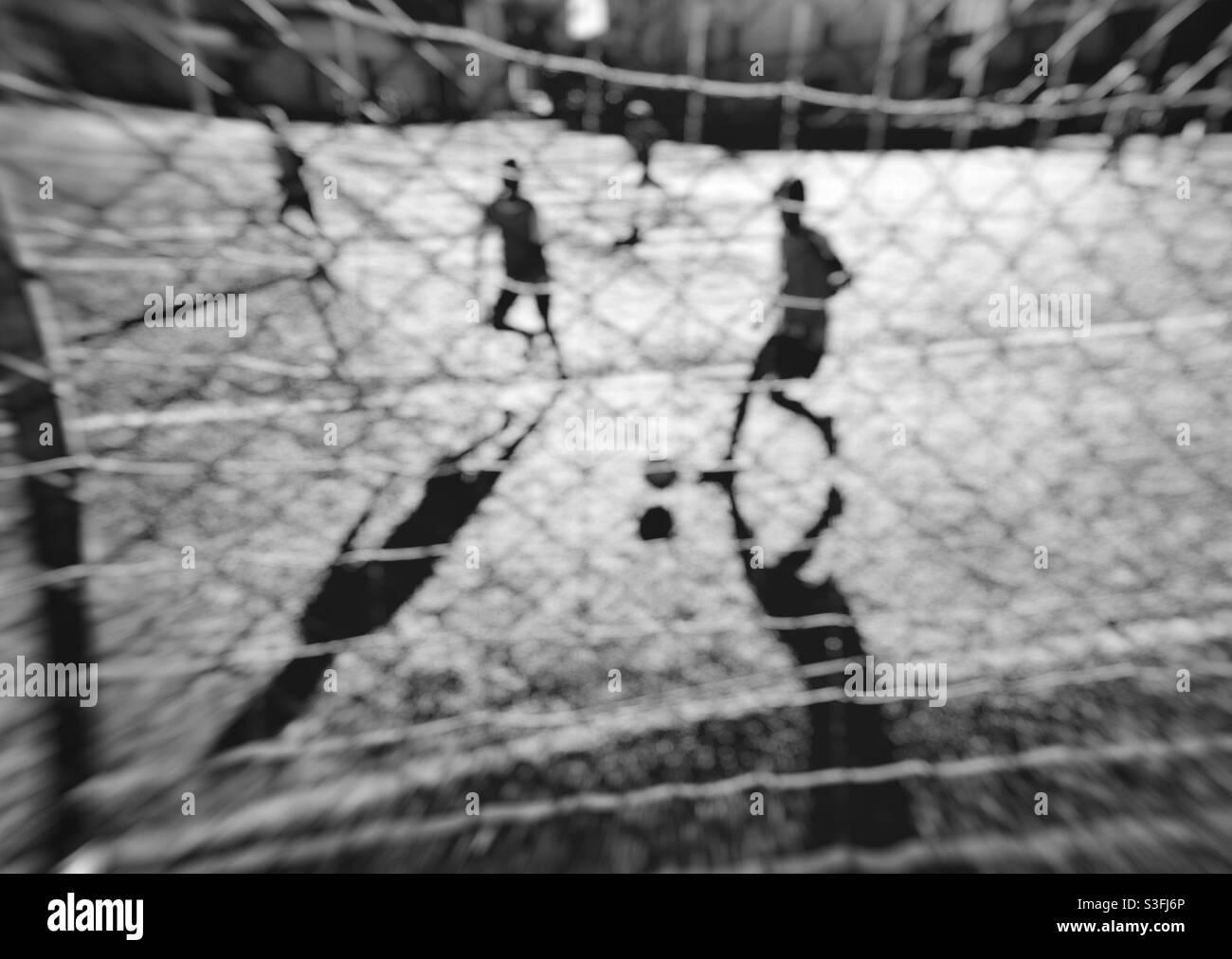 Visione monocromatica dei giovani che giocano a calcio. Foto Stock