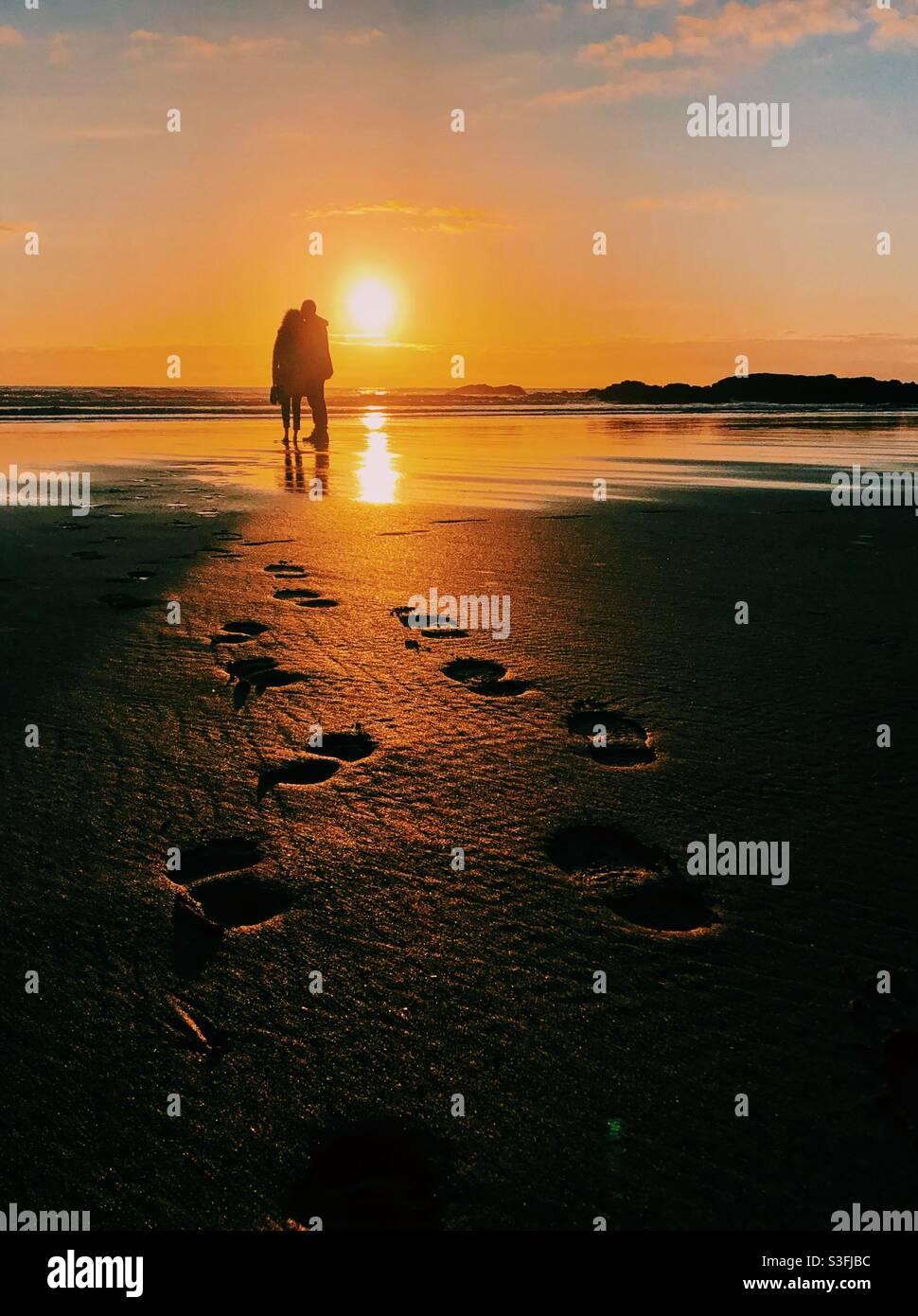 Una coppia ha silhoueted guardando il tramonto su una spiaggia, le impronte dei piedi che li conducono Foto Stock