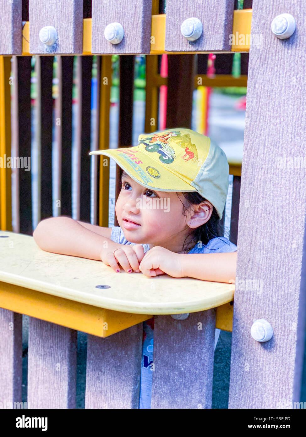 Bambina al parco giochi sognando via Foto Stock