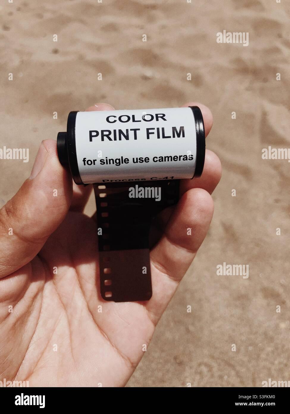Un rotolo di pellicola a colori da 35 mm a portata di mano contro sabbia sfondo Foto Stock