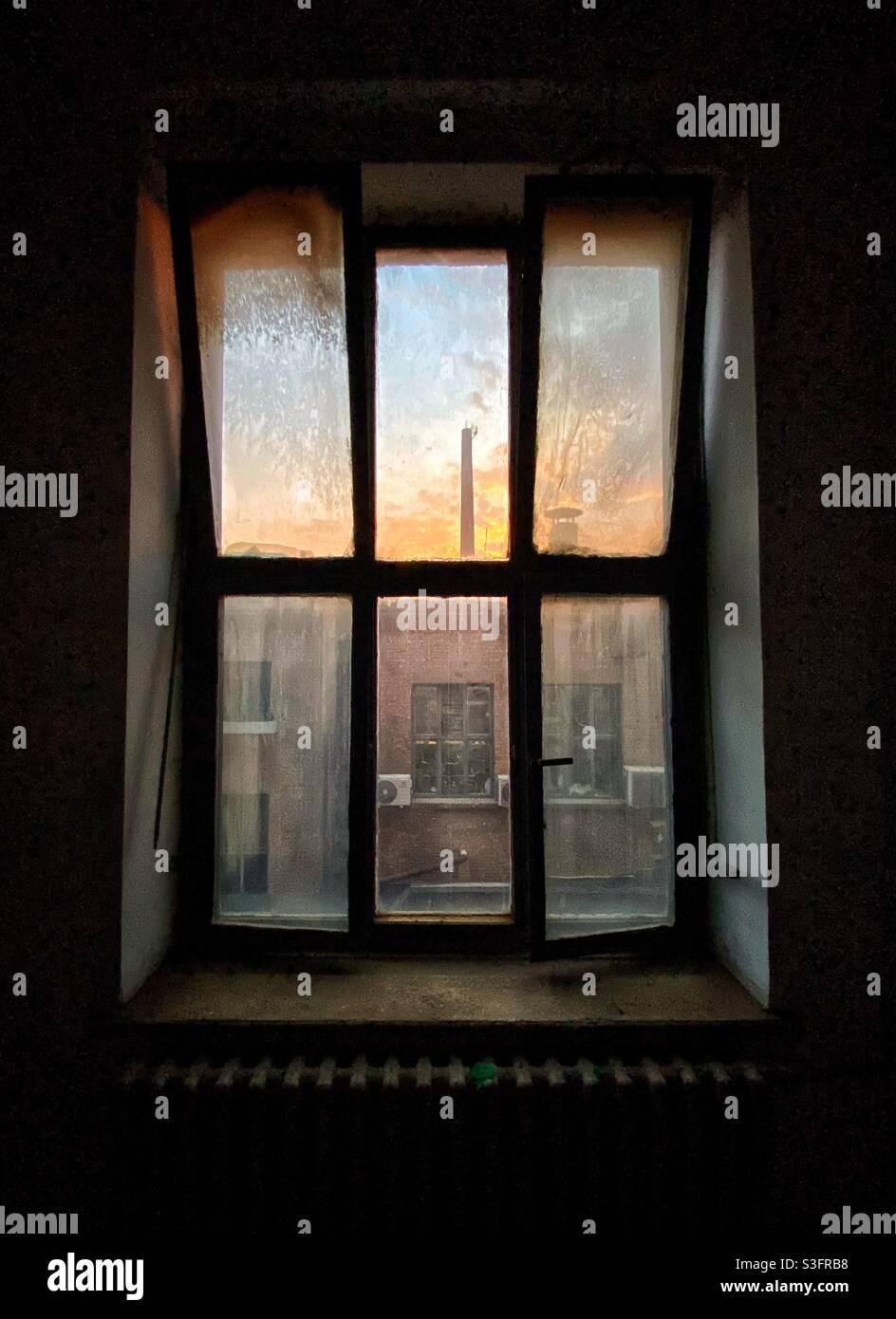 Vecchia finestra sporca con cielo tramonto e tubo di fabbrica Foto Stock