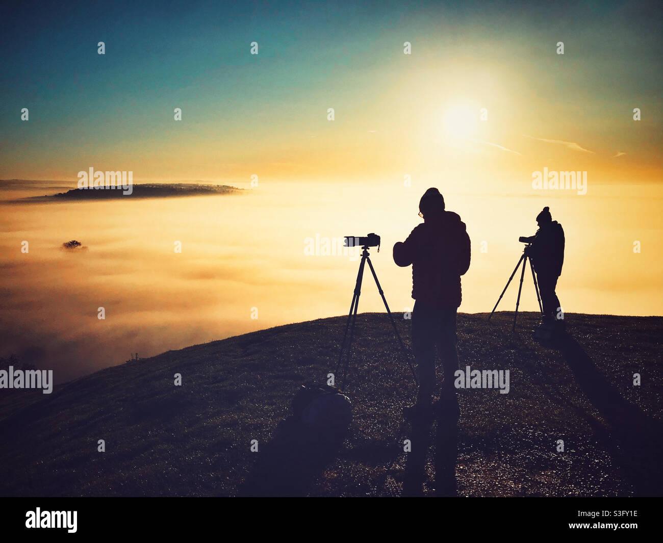 I fotografi hanno allestito fotografando le nebbie mattutine di Avalon da Glastonbury Tor, Somerset Foto Stock