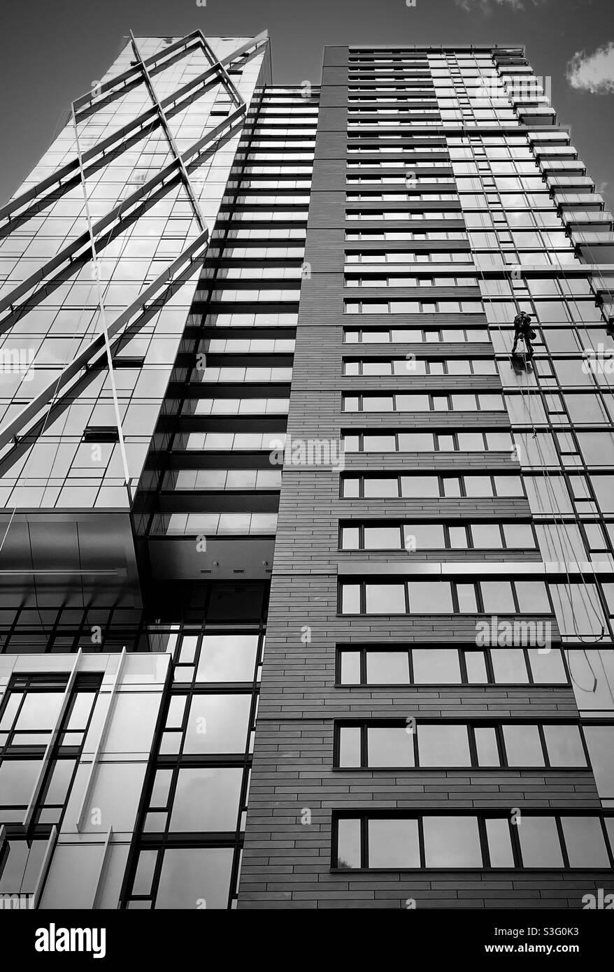 Una lavafinestre in alto che lava un edificio nuovo e moderno. Vancouver, British Columbia. Canada. Foto Stock