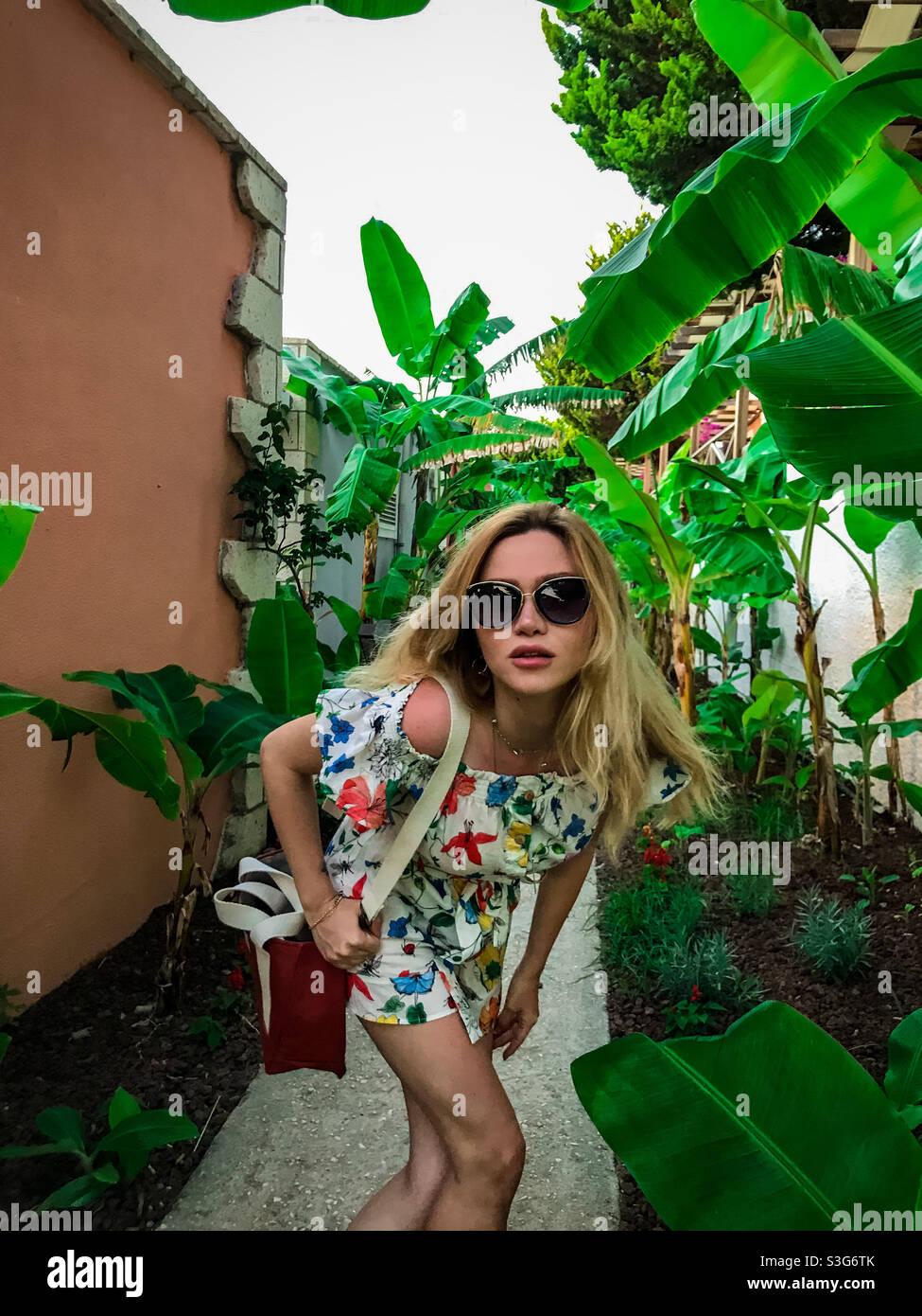 Bella e bionda modella ragazza si arrabbia al suo fotografo tra le foglie tropicali di banana. Foto Stock
