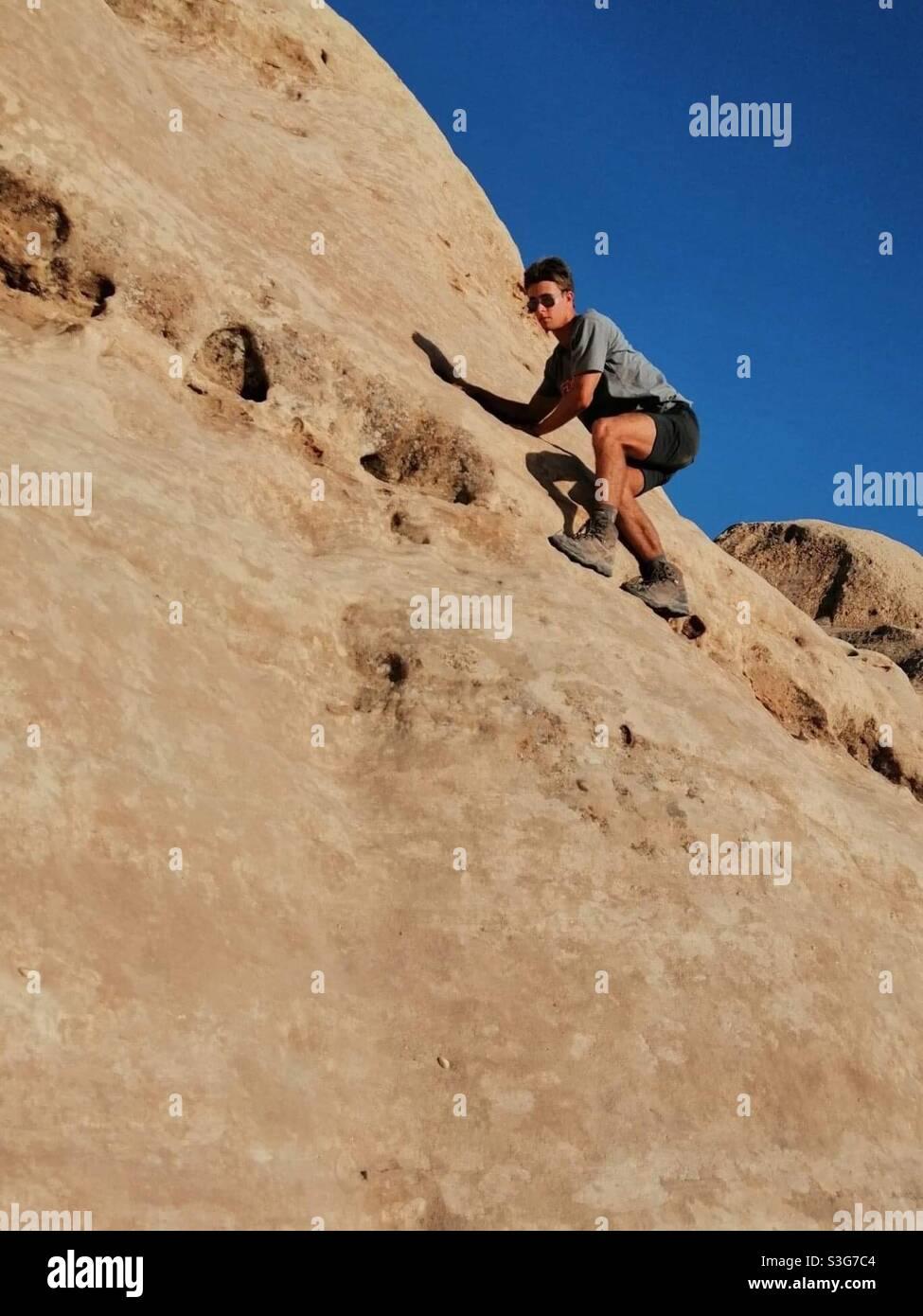 Un uomo che arrampica rocce a Petra, Giordania. Foto Stock