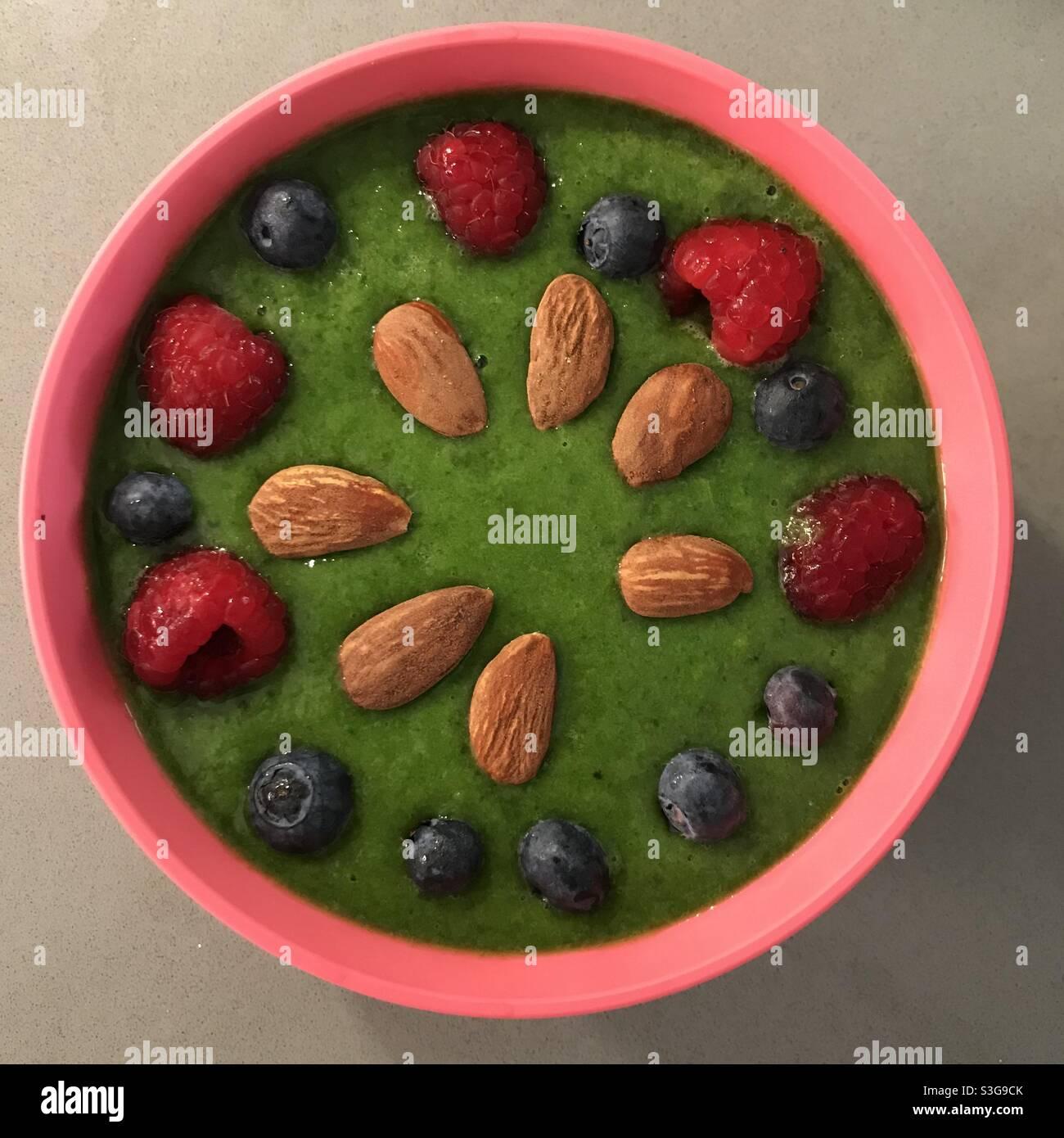 Colazione verde e sana, con frutta rossa e mandorle Foto Stock