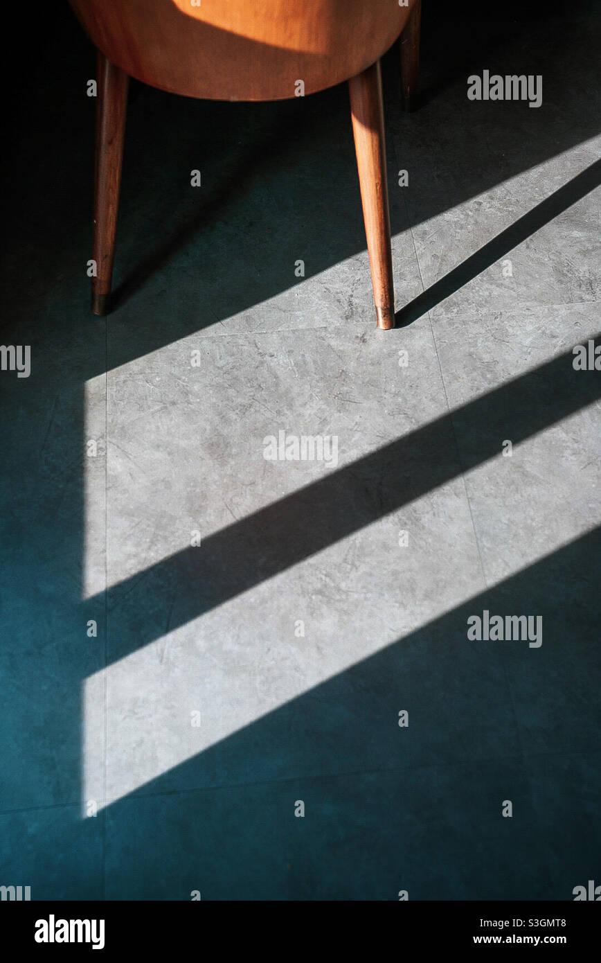 La luce si rompe attraverso una finestra creando linee diagonali spezzate dalla gamba della sedia Foto Stock