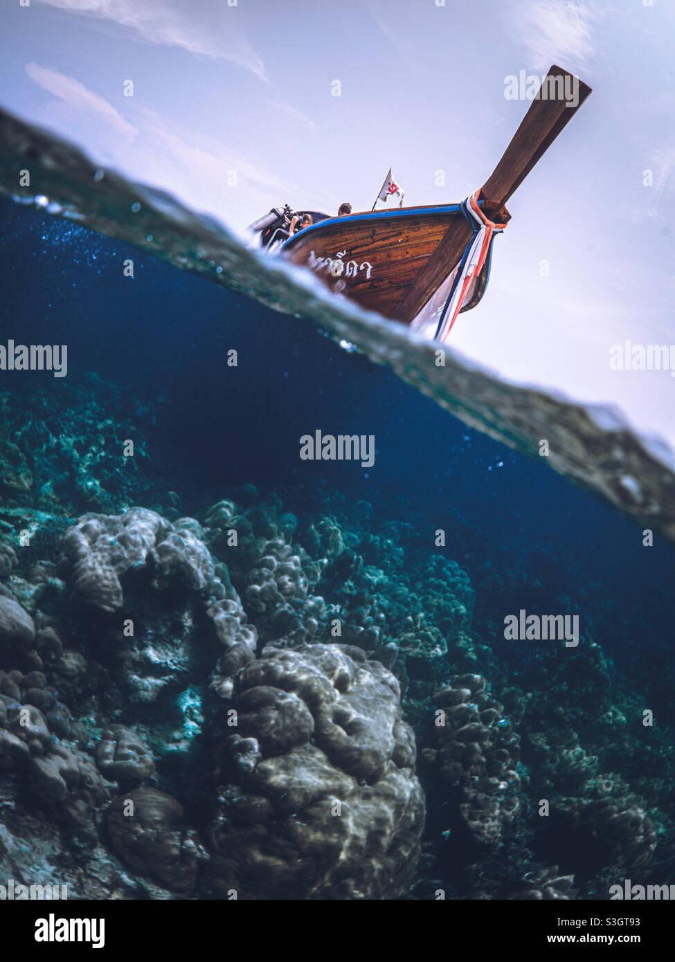 Lunga coda di legno barca tipic fromThailandia andare a snorkeling in acque blu e limpide Foto Stock