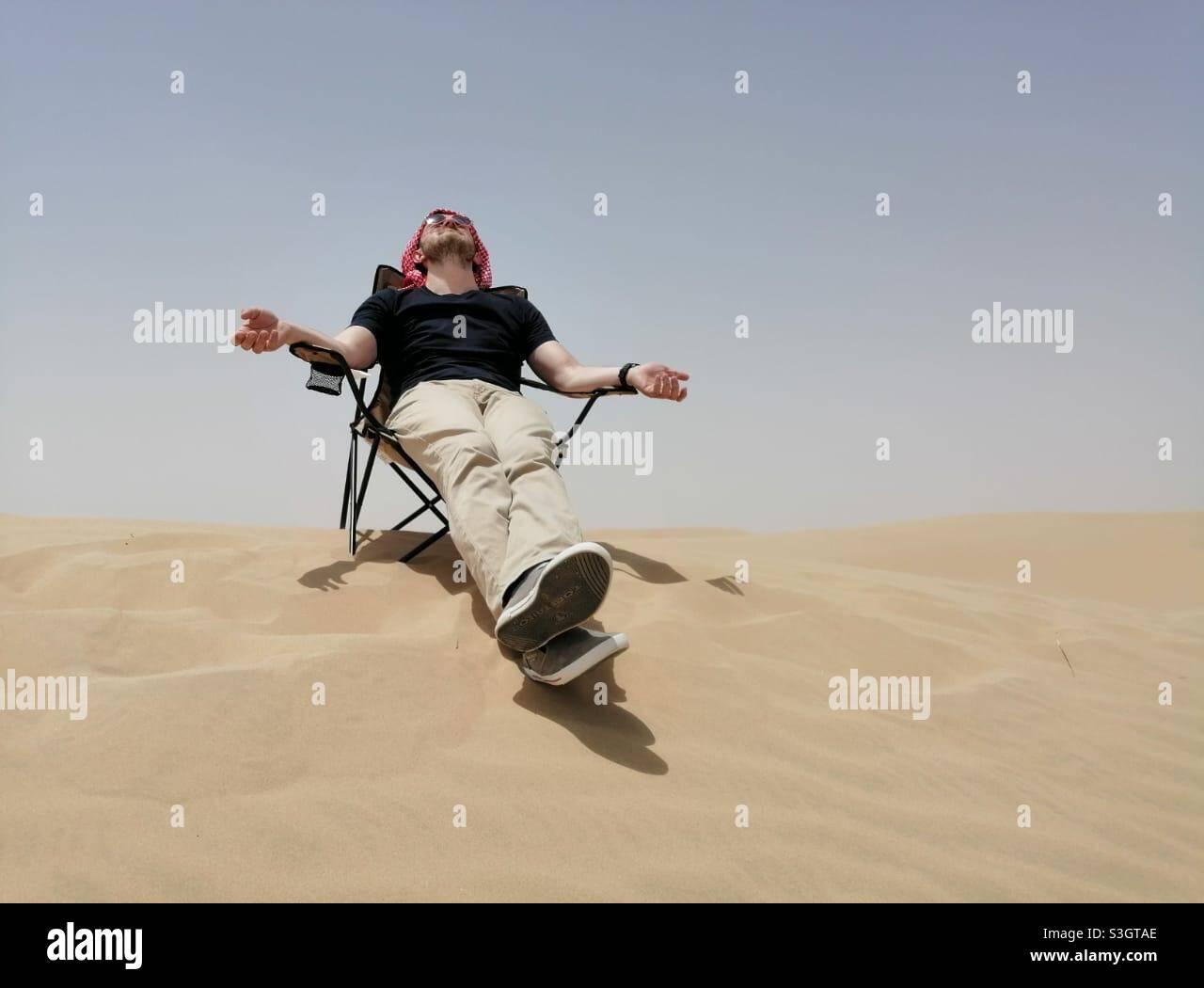 L'uomo turistico gode del sole mentre si siede su una sedia nelle dune di sabbia del deserto a Dubai, Emirati Arabi Uniti. Foto Stock