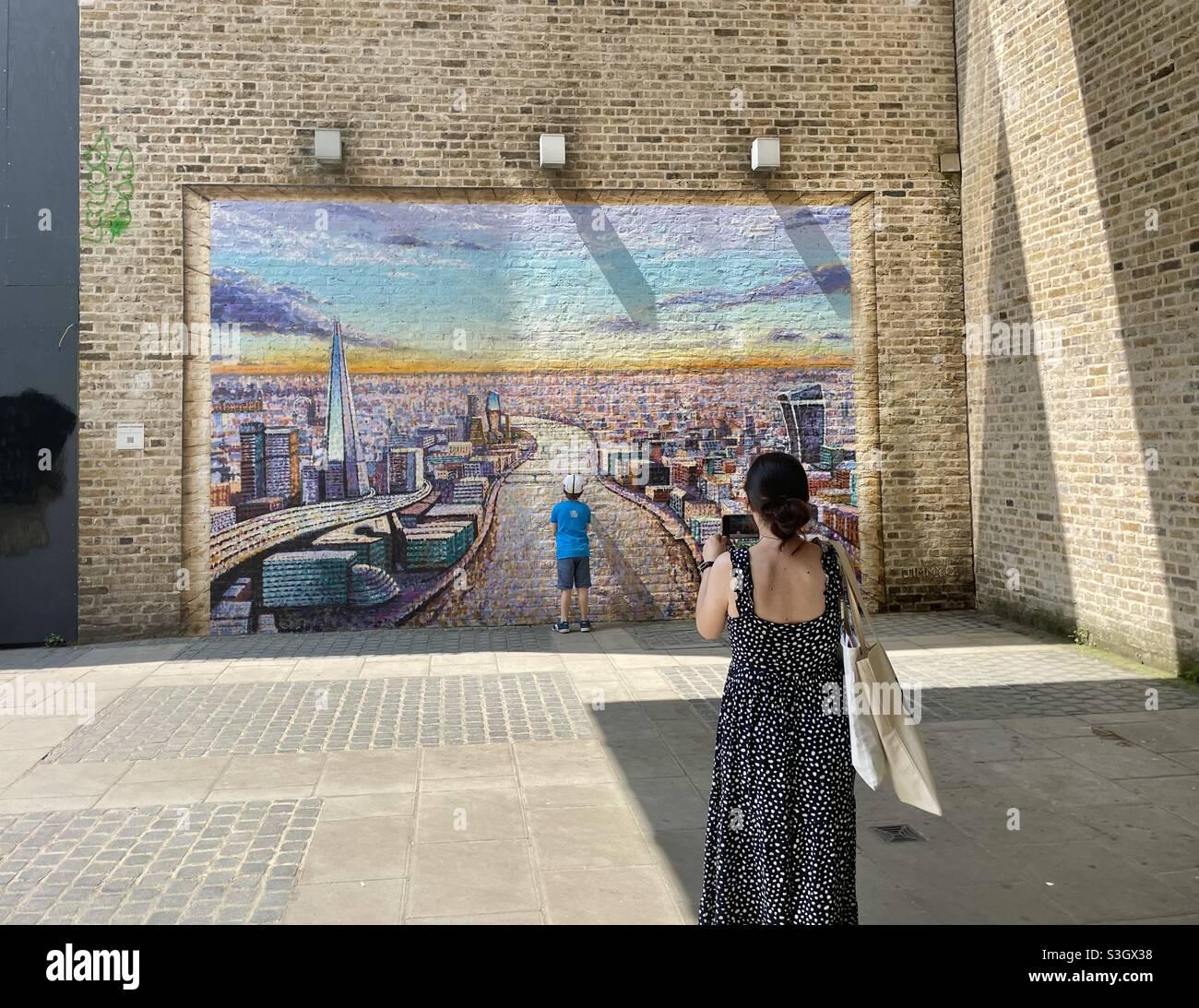 Donna fotografa il suo giovane sole di fronte a una morale di londra sulla riva sud Foto Stock