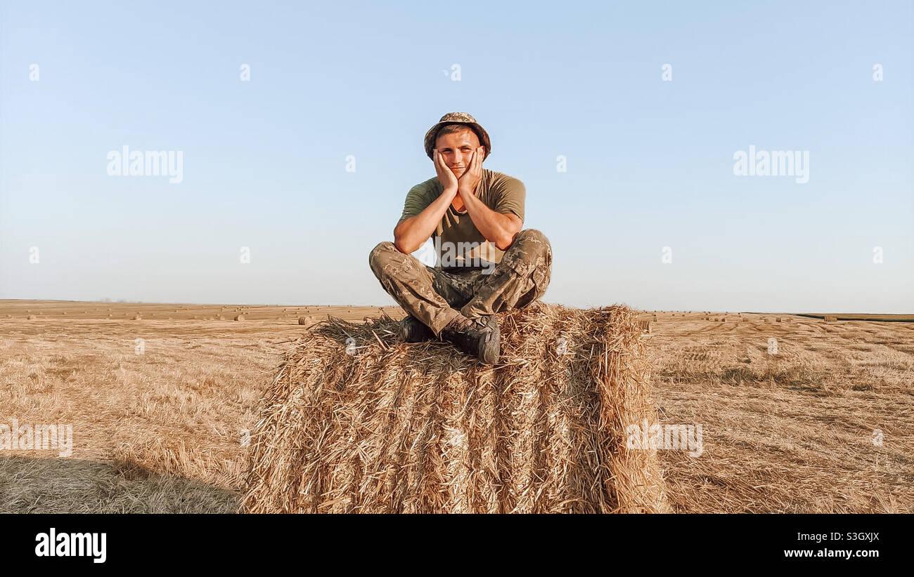 Ragazzo di campagna seduto su un pagliaio Foto Stock