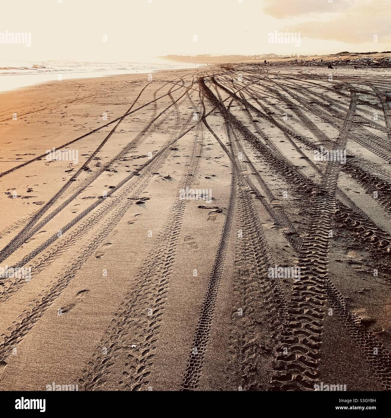Piste di pneumatici nella sabbia di Castlecliff Beach in Nuova Zelanda Foto Stock
