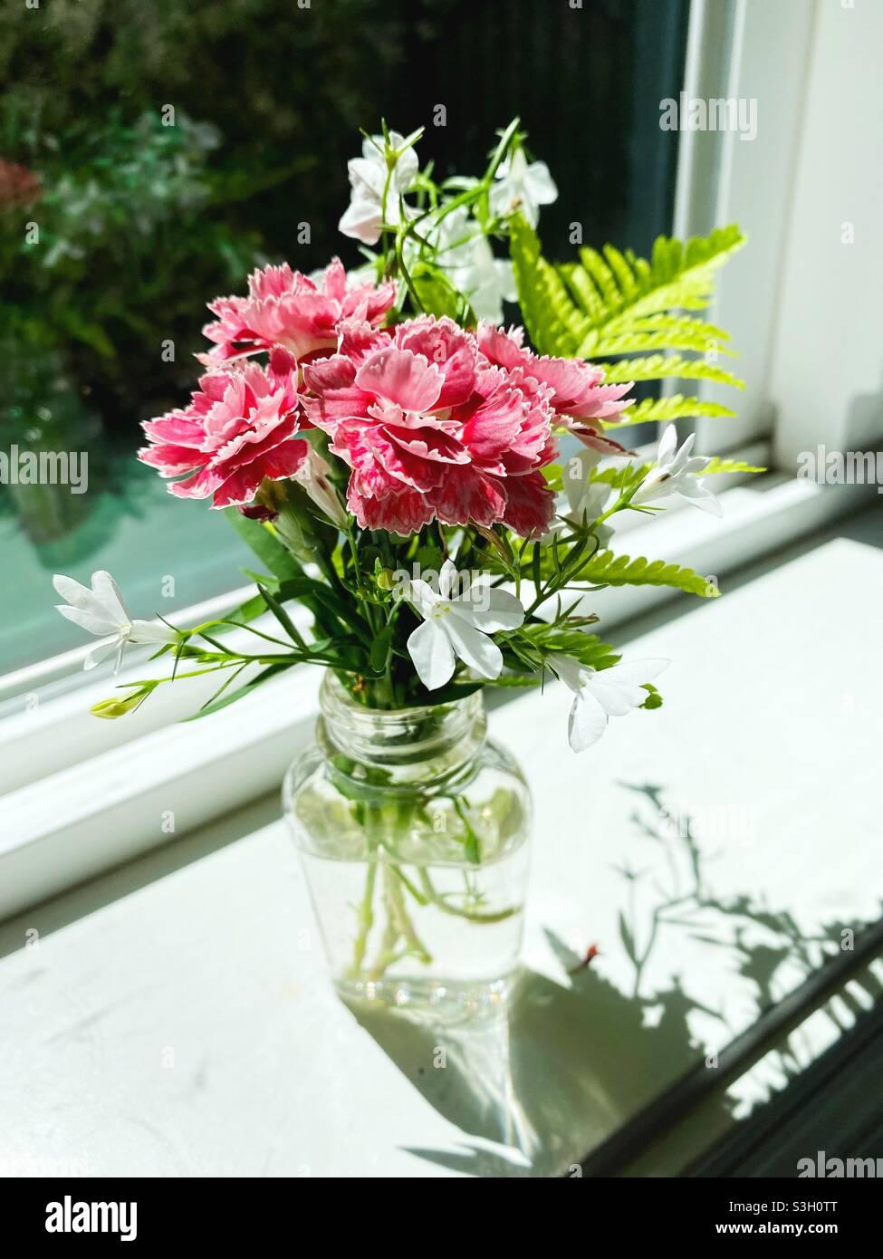 Un piccolo vaso di vetro con una bella disposizione di fiori su un davanzale della finestra. Foto Stock