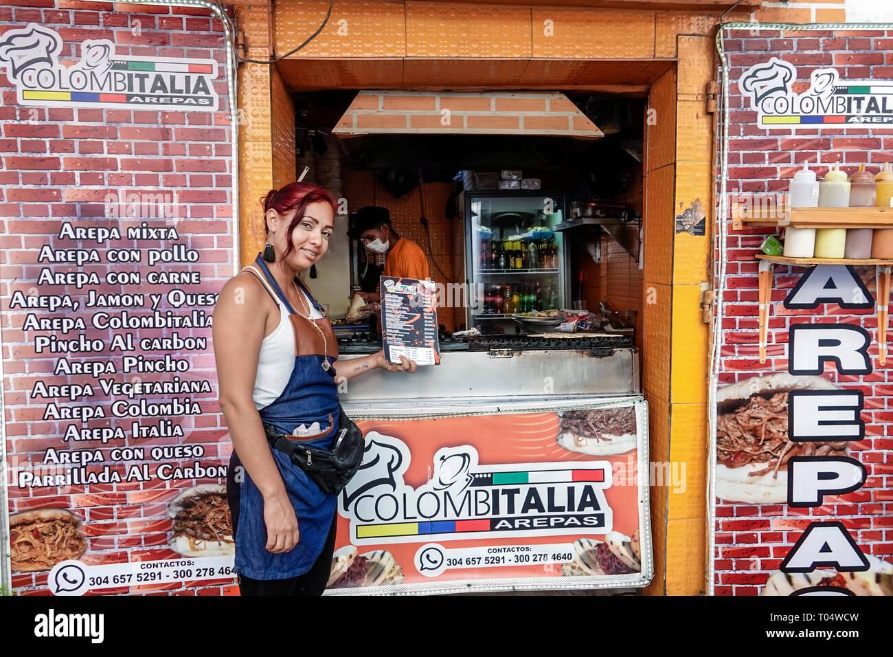 Cartagena Colombia antica città murata centro Getsemani ispanici residenti residenti donna che offre menu stand arepas di stallo menu vendor manager Immagini Stock