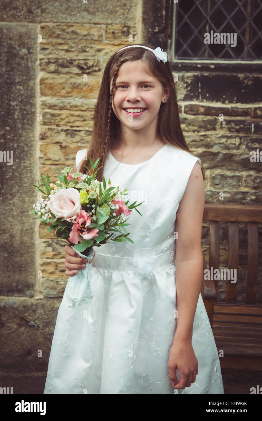 24718cc4d91e Bella sorridente tween o teen giovane damigella tenendo un rustico bouquet  di fiori selvaggi