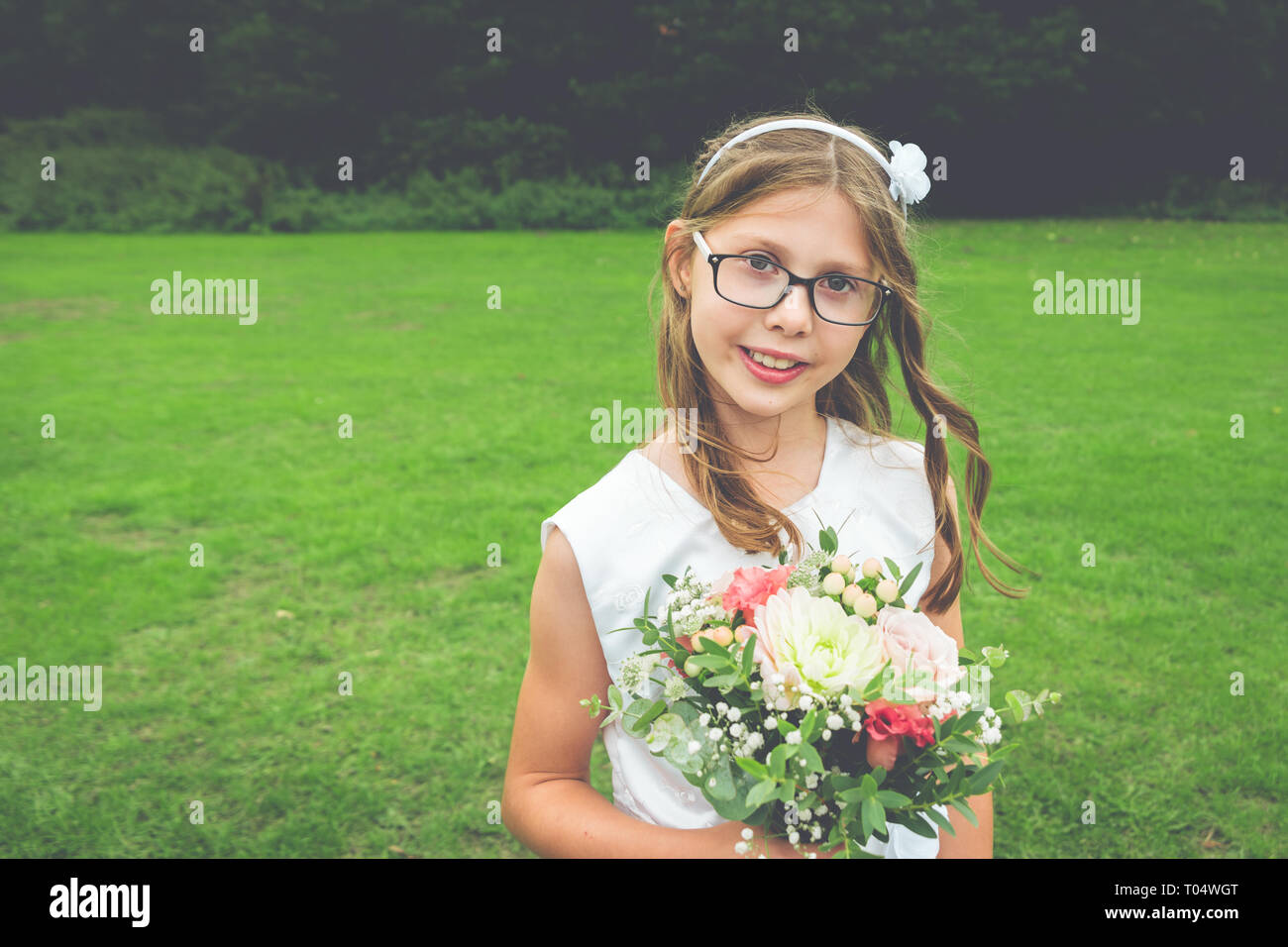 412134f01943 Ragazza dolce bambino damigella in abito bianco e i bicchieri con fiori  selvaggi e vegetazione posy -