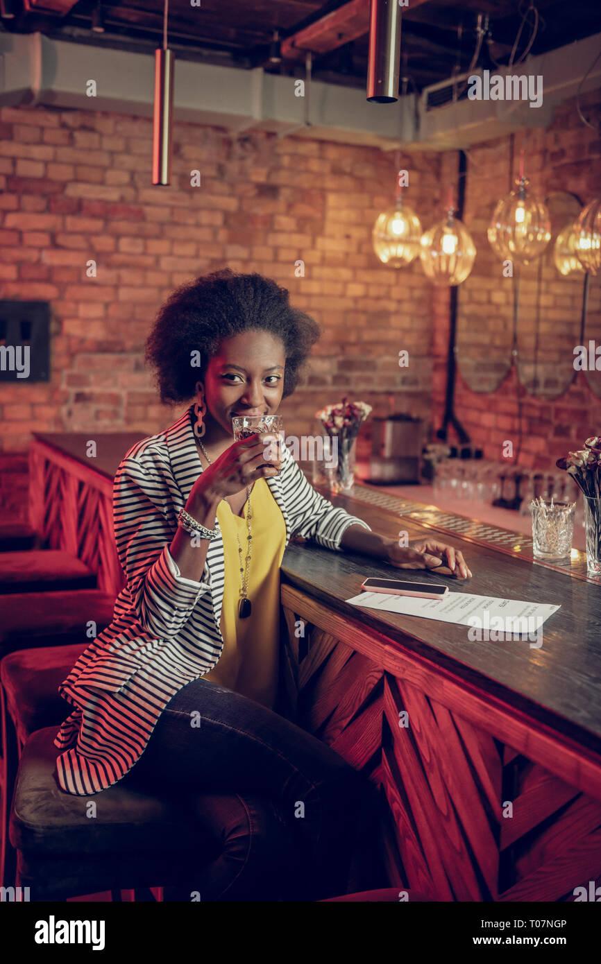 Grazioso bella dai capelli scuri di venti anni afro-americano di mademoiselle avente drink al bar Immagini Stock